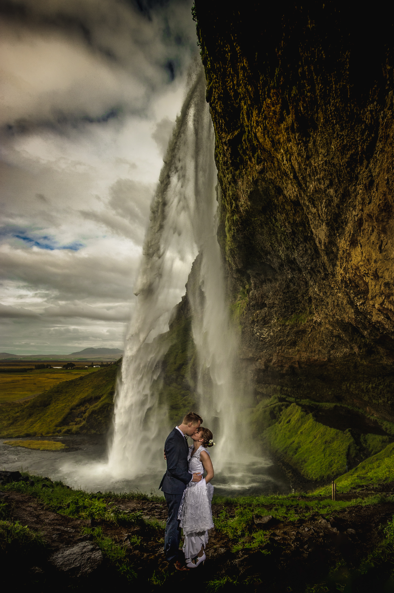Landscape couple portrait under waterfall against dramatic sky - photo by Viridian Images Photography