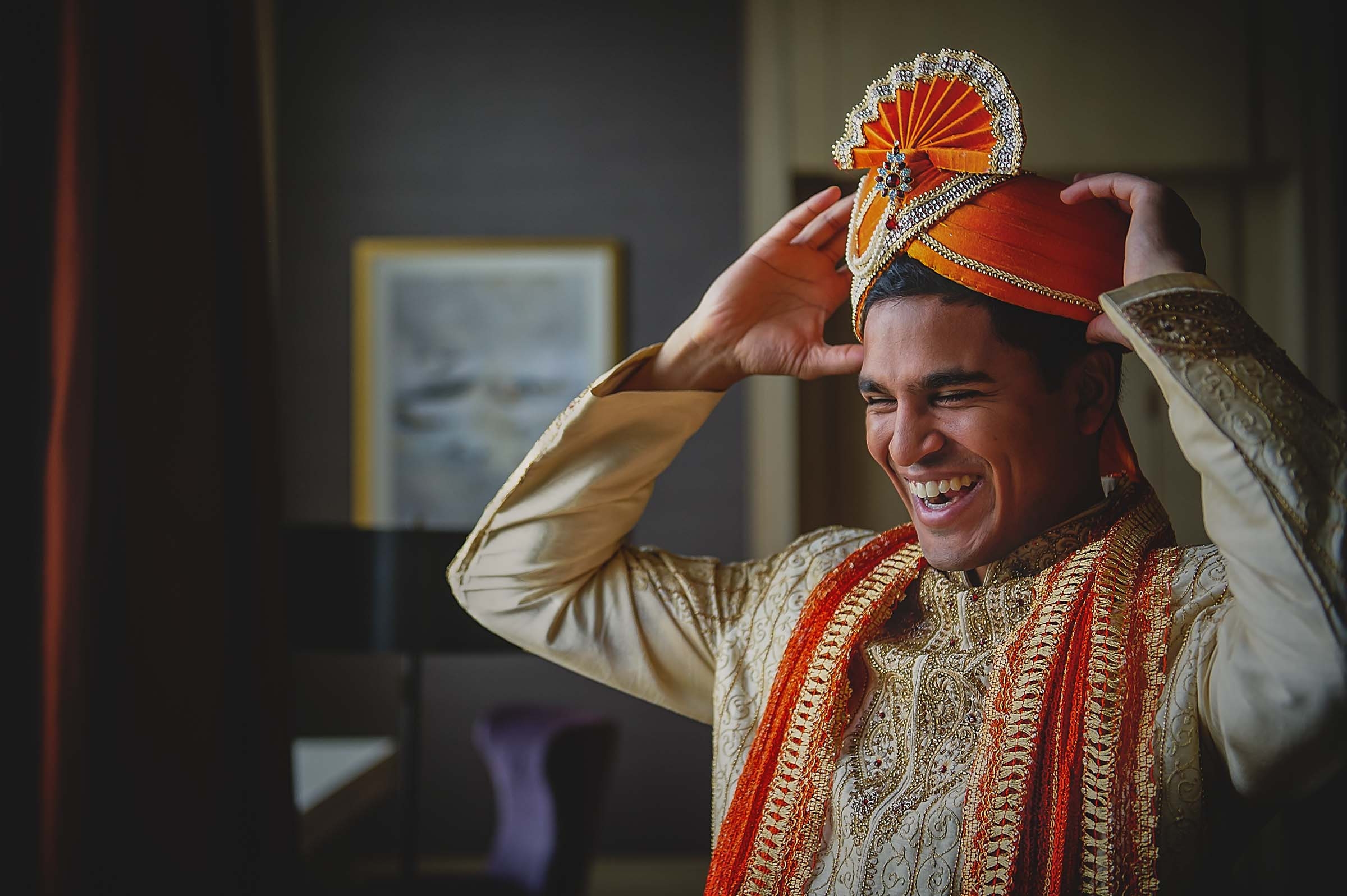Smiling  groom putting on hat - photo by Viridian Images Photography