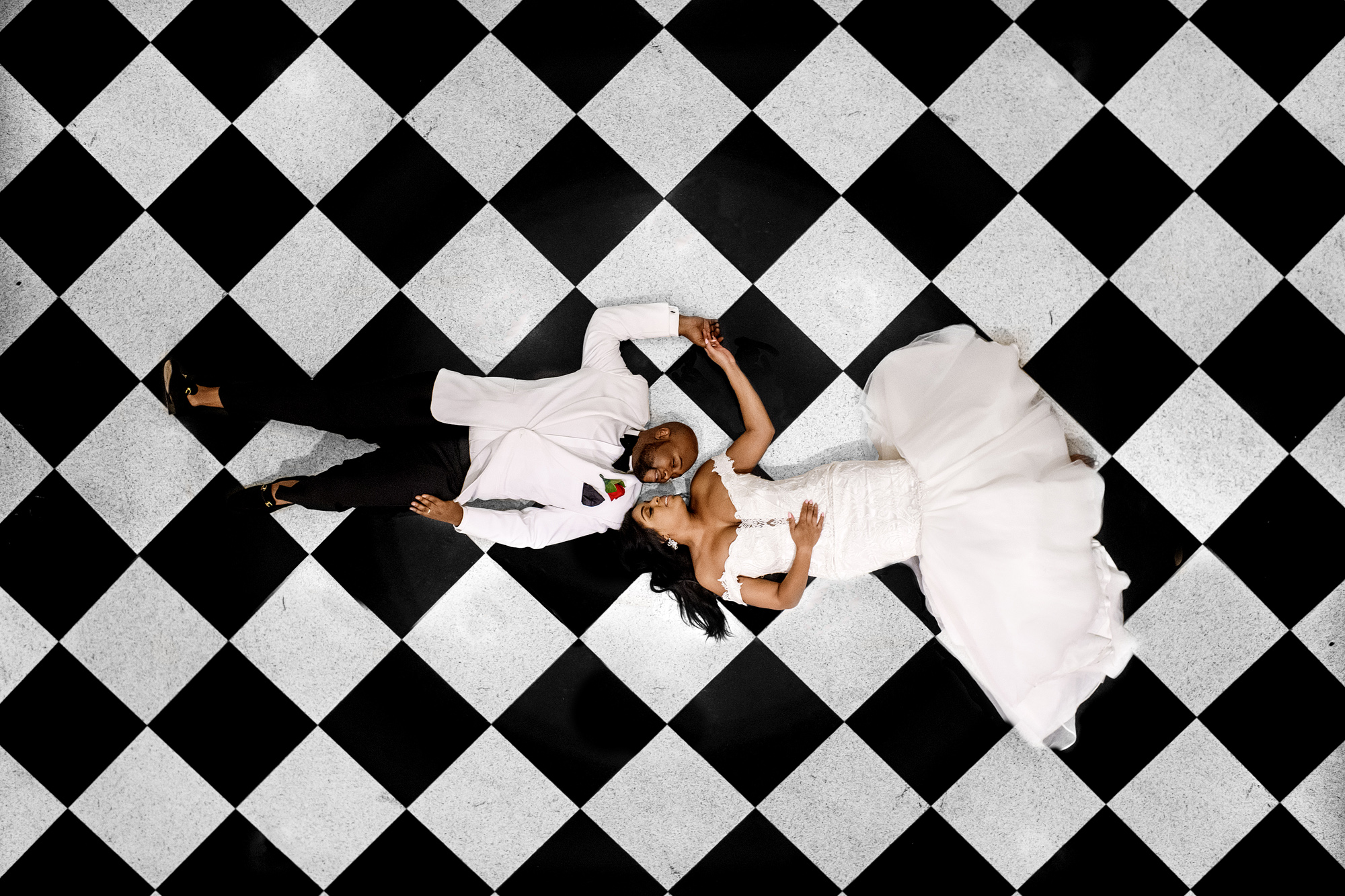 Aerial view of couple on black and white checked floor - photo by Joshua Dwain Photography