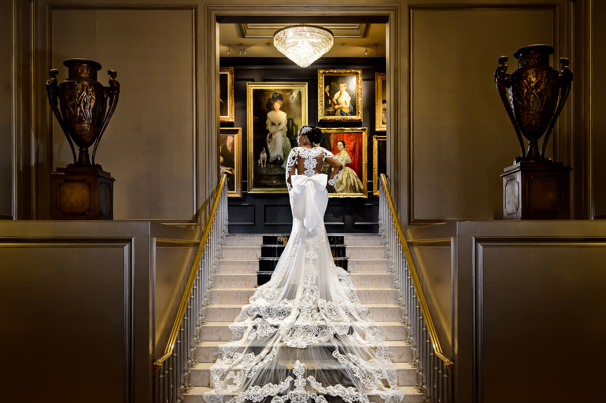 Bride with long lace train on elegant stairway - photo by Joshua Dwain Photography