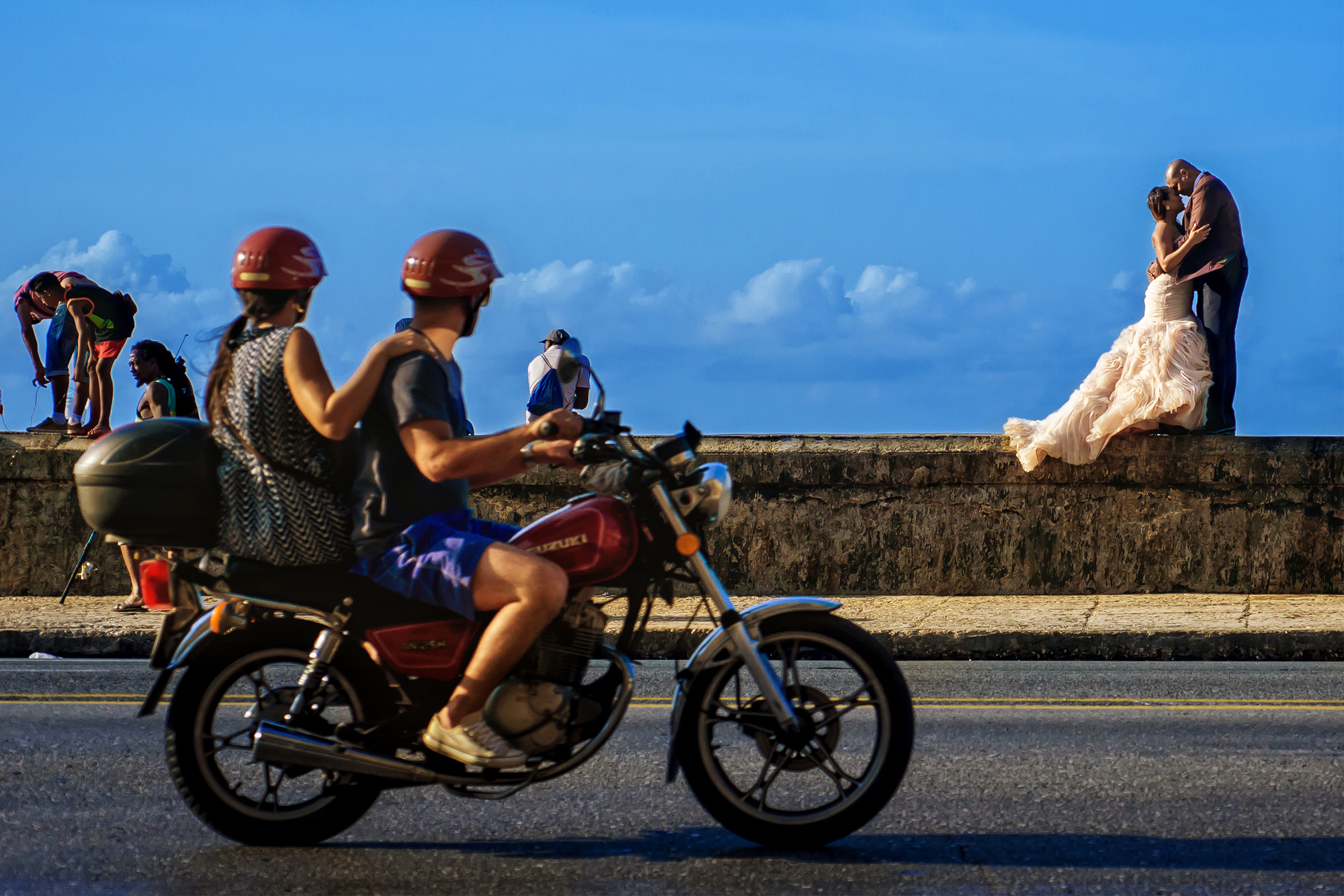 Couple kiss on sea wall with motorbike passing - photo by Joshua Dwain Photography