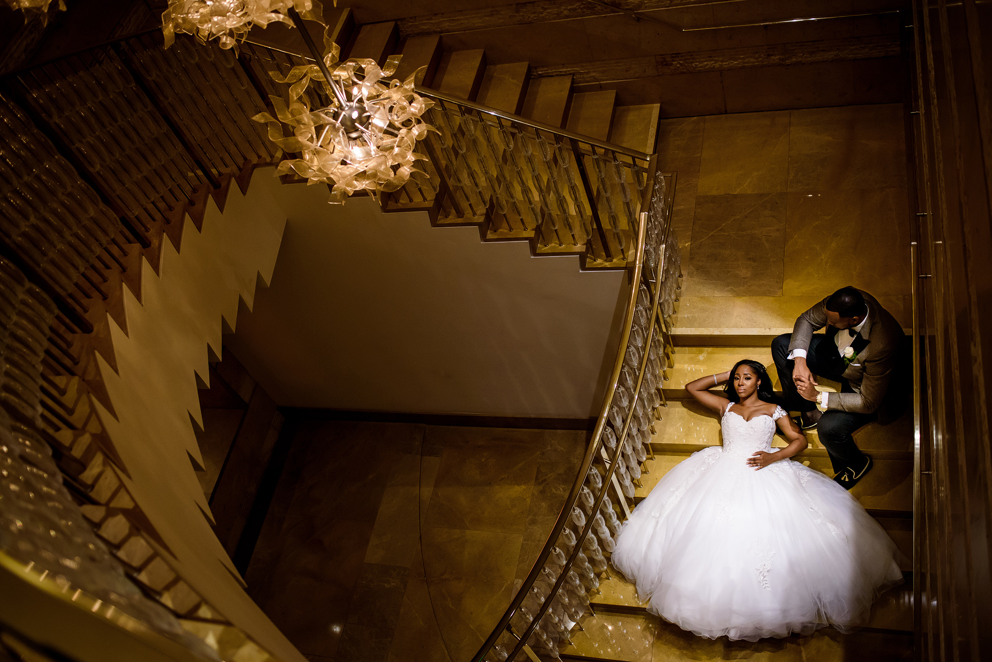 Couple on golden stairway - photo by Joshua Dwain Photography