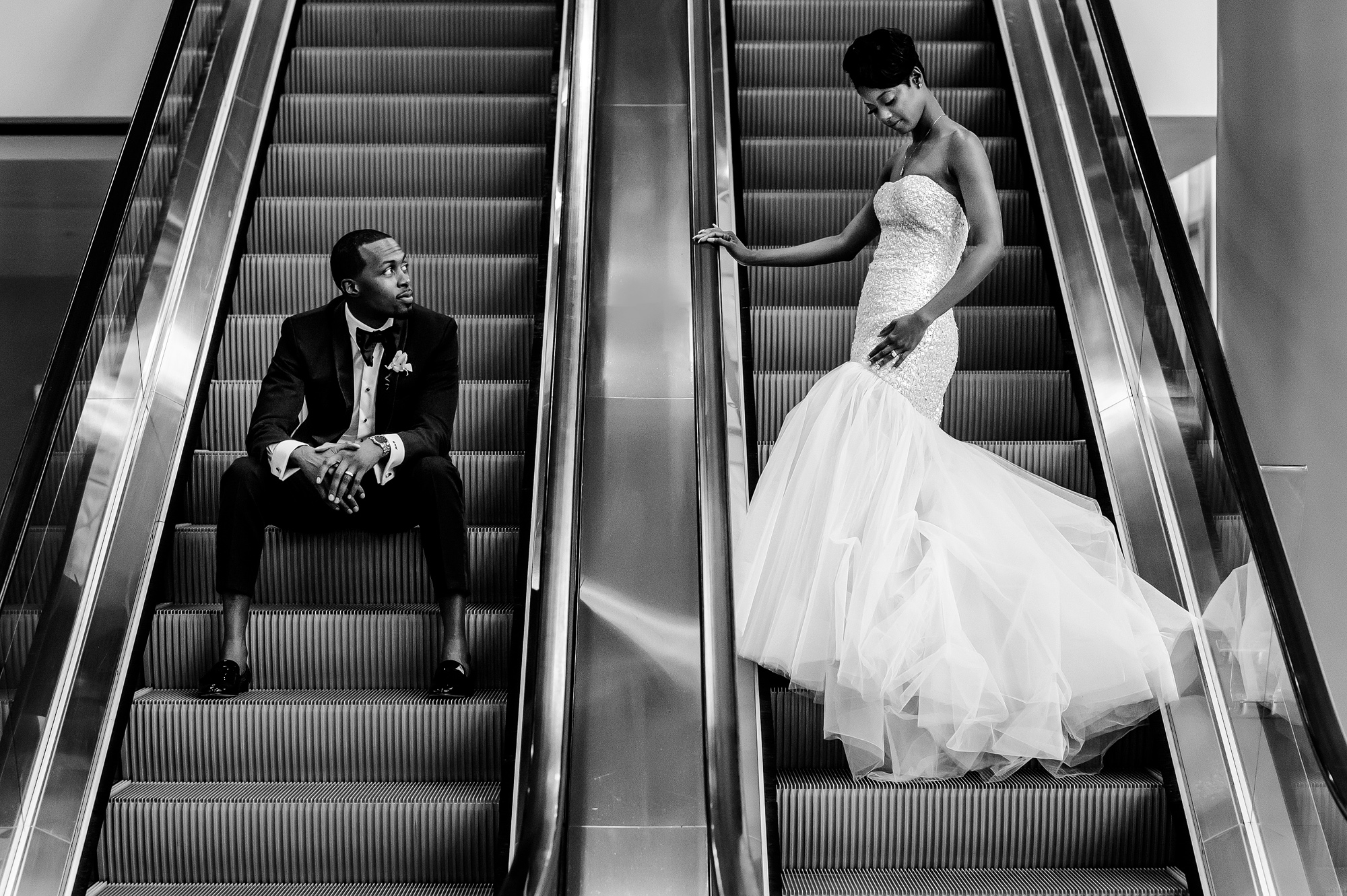 groom and bride wearing strapless trumpet dress on escalator - photo by Joshua Dwain Photography