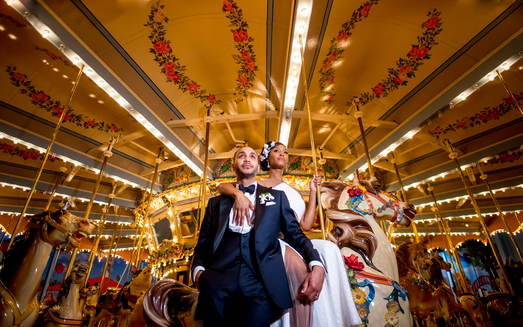Bride and groom posing against a carousel - photo by Adibe Photography