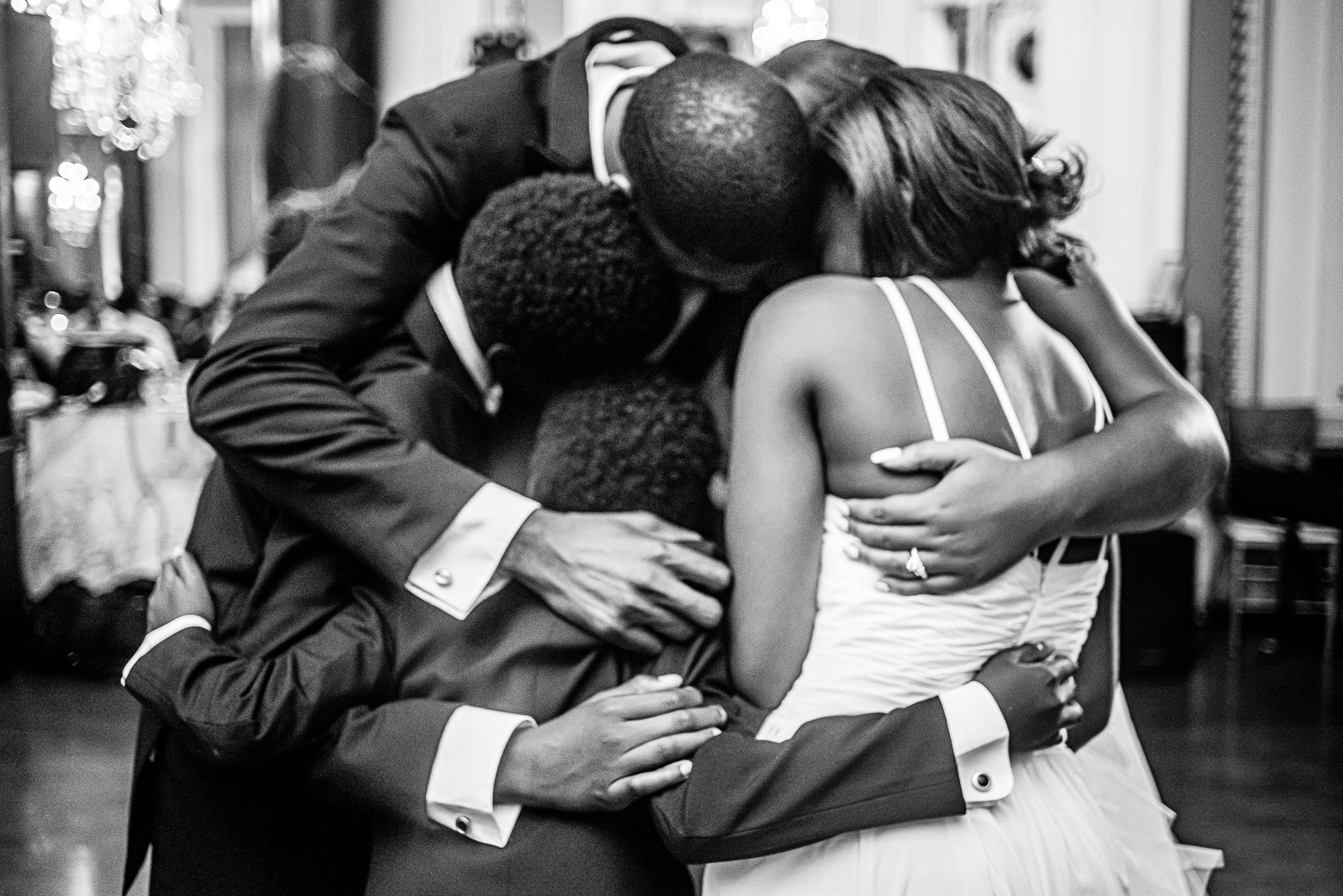 Bride, groom and family hugging - photo by Adibe Photography