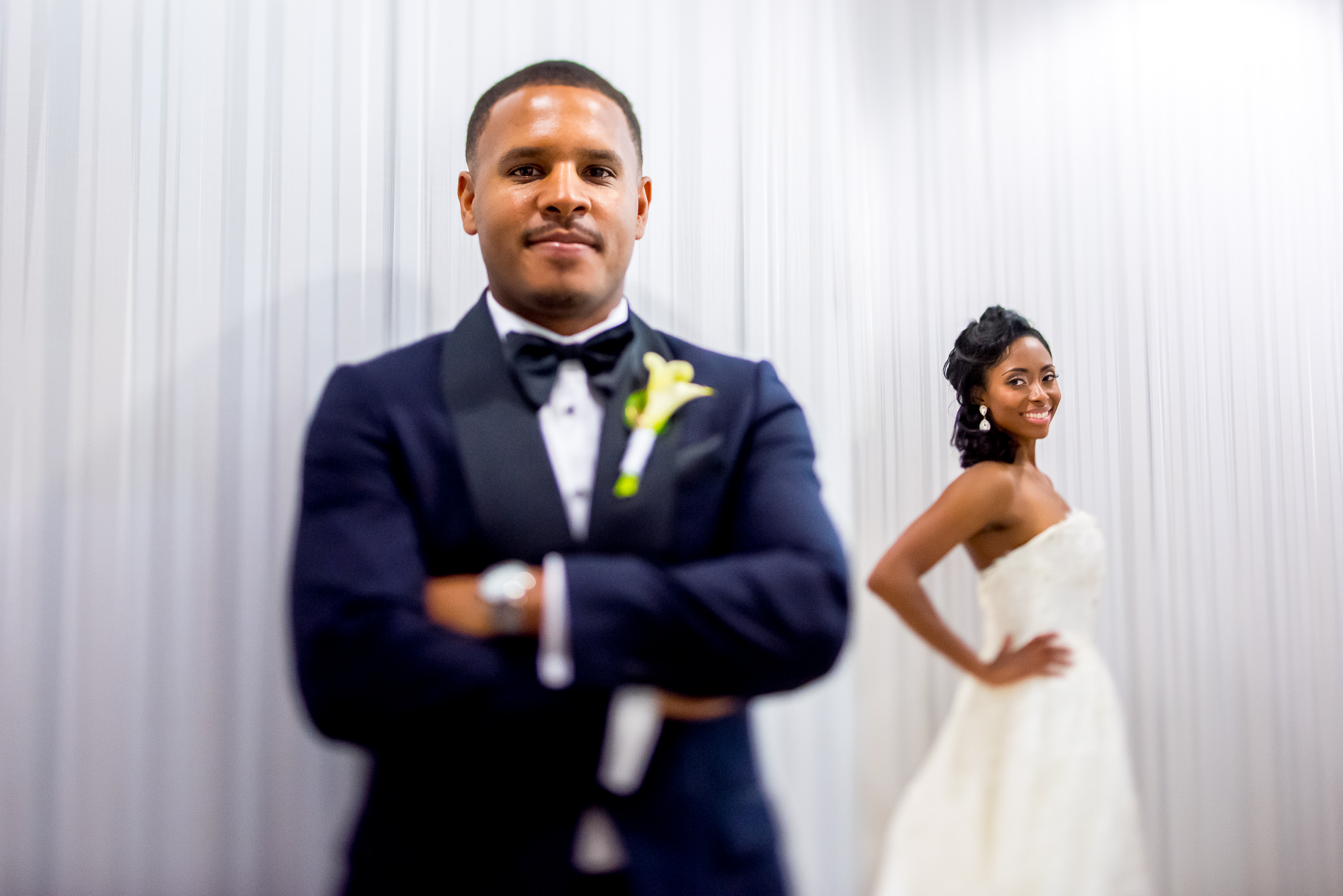 Groom in foreground, bride in background portrait - photo by Adibe Photography