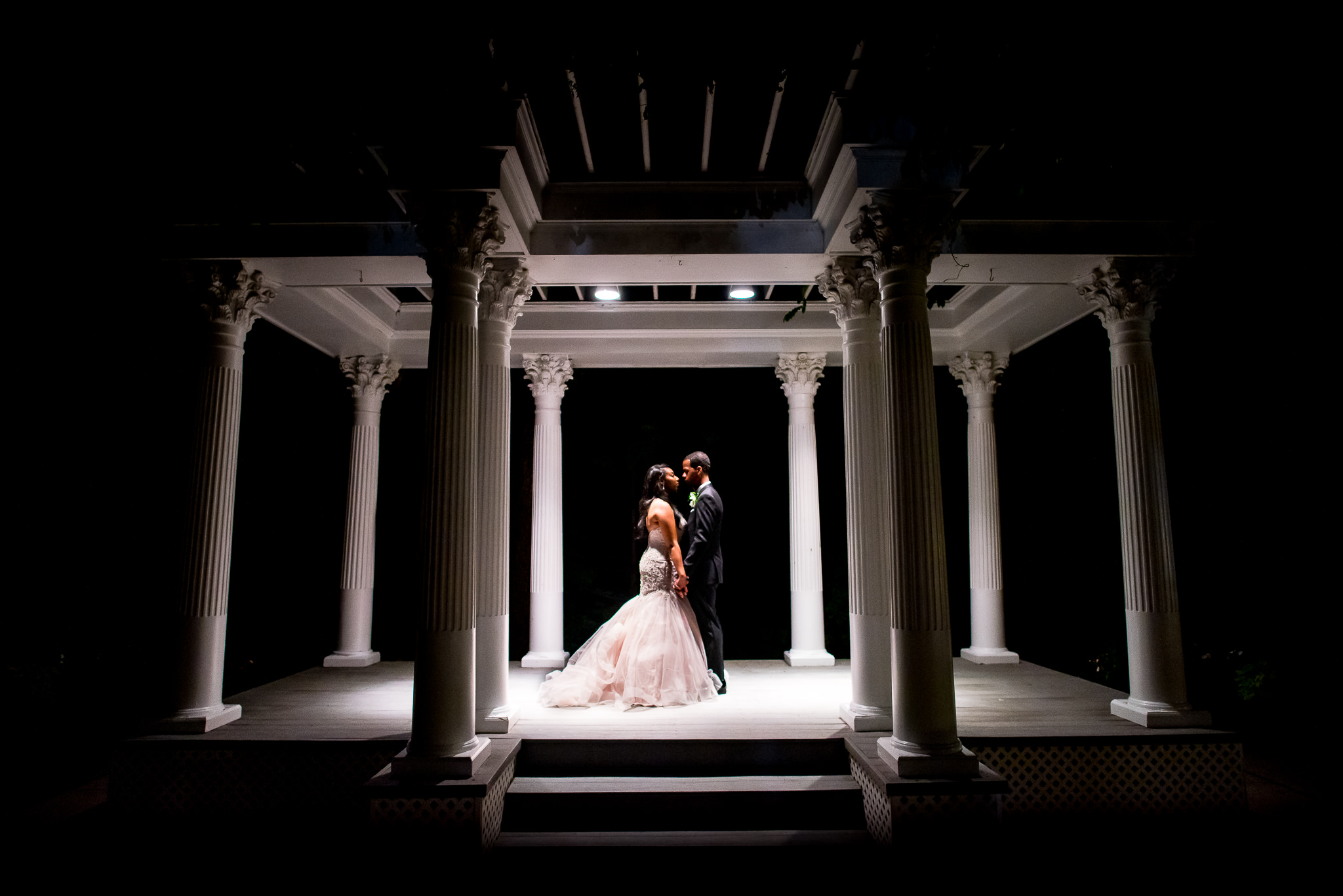 Nighttime bride and groom portrait under gazebo - photo by Adibe Photography