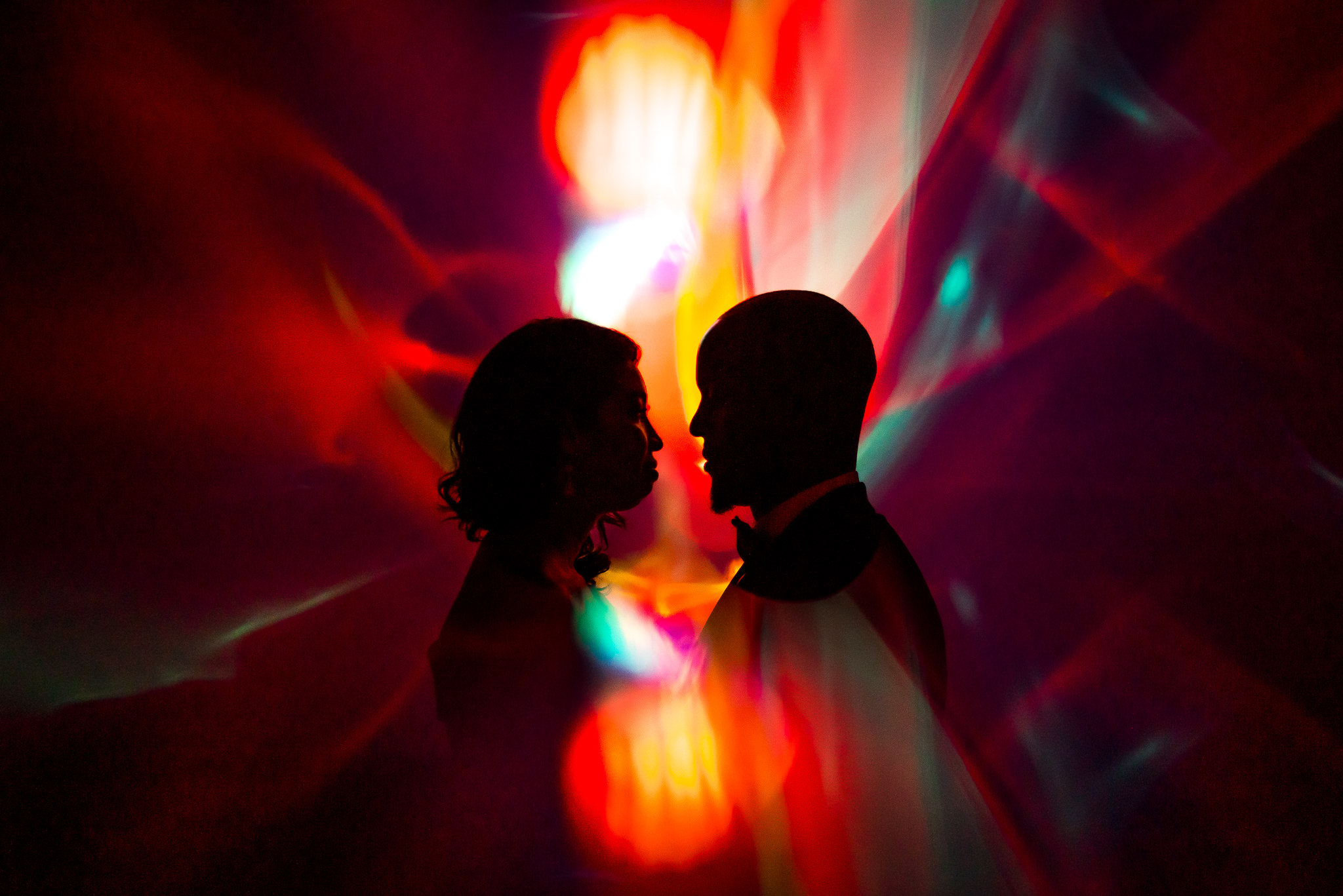 Silhouette of bride and groom against colorful lights - photo by Adibe Photography