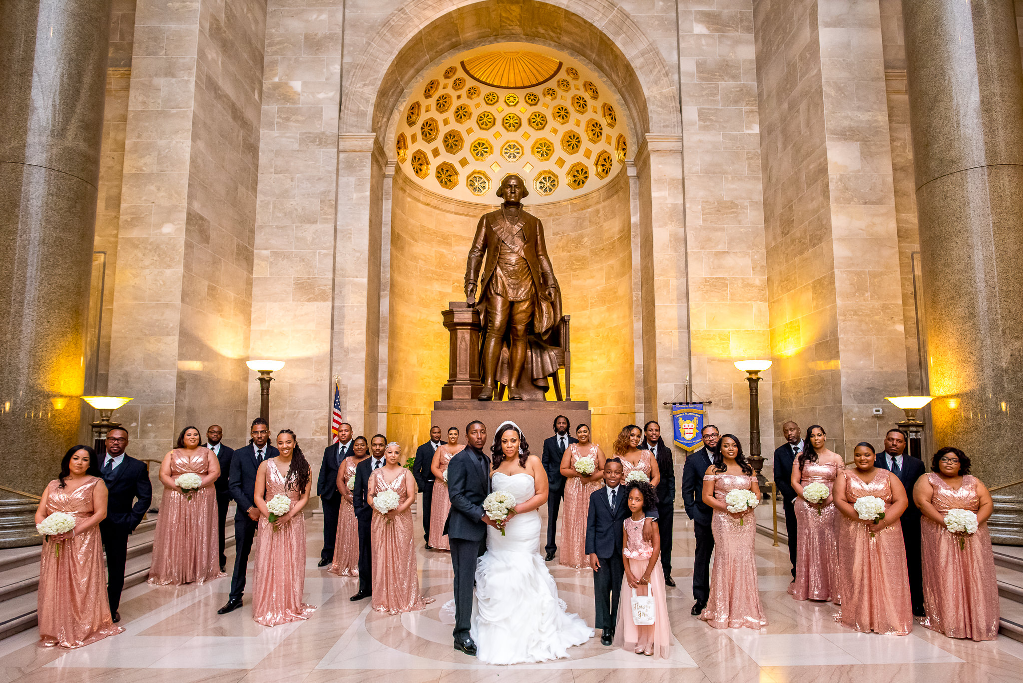 Wedding party group pose against statue in alcove- photo by Adibe Photography