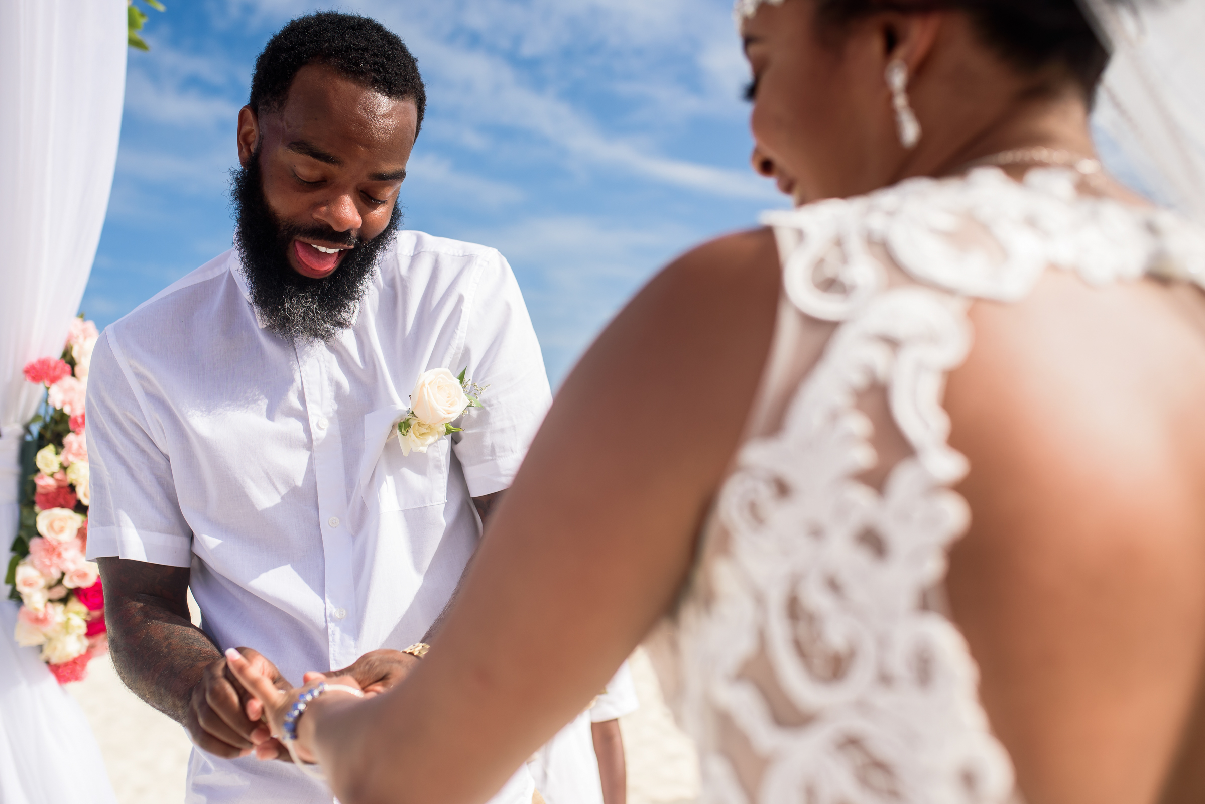 Groom puts ring on bride in outdoor ceremony - photo by Ashleigh Bing Photography