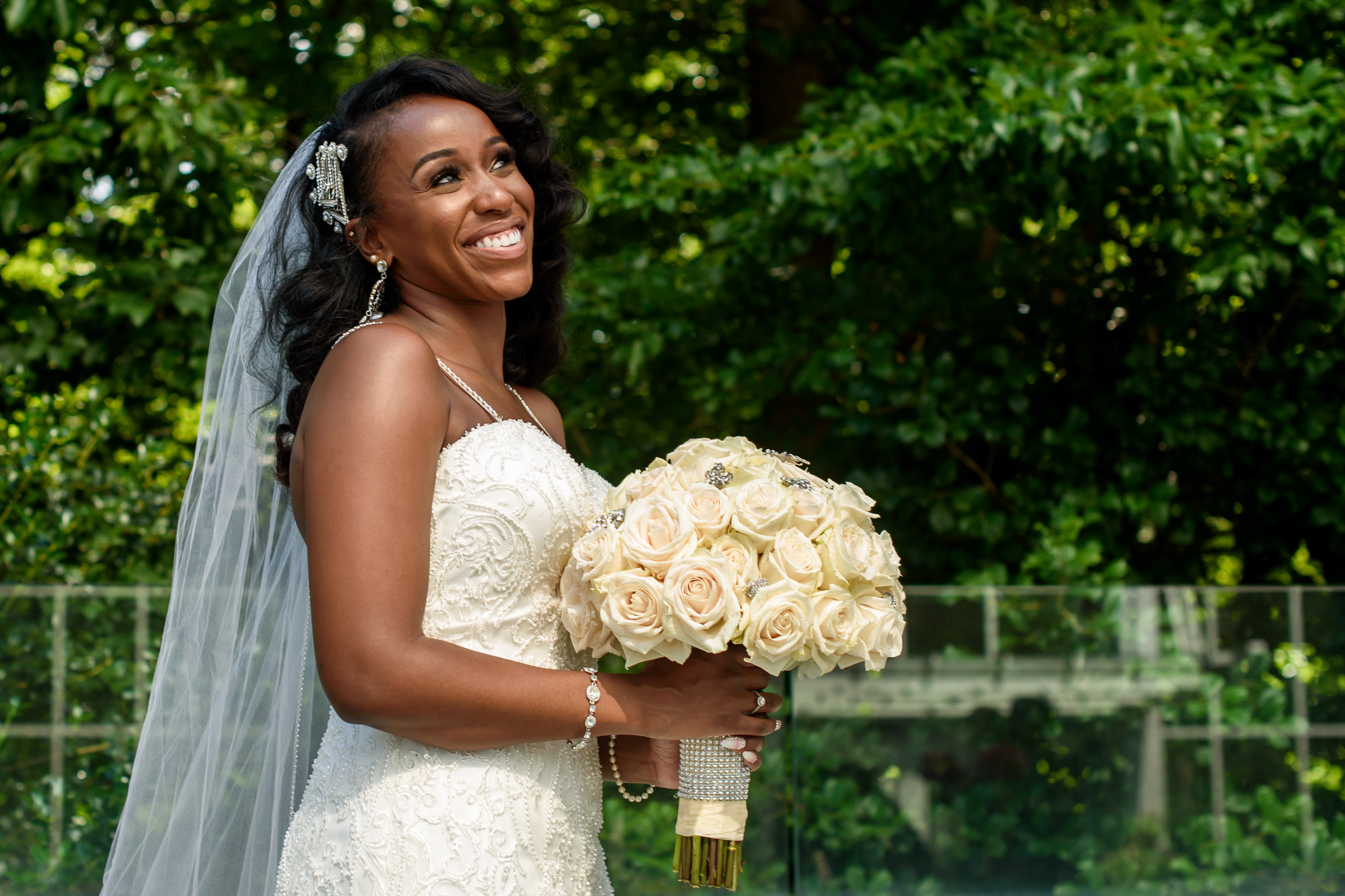 Smiling bride with bouquet of white roses - photo by Ashleigh Bing Photography