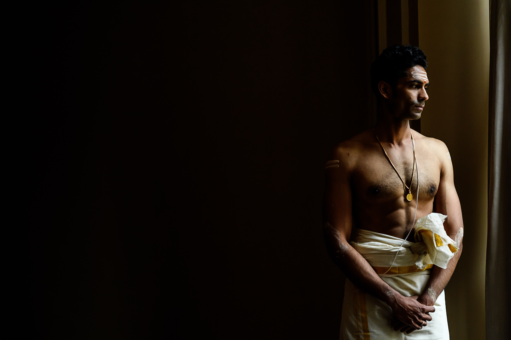 Bare chested Indian groom in traditional-garb in window light -  photo by Christopher Jason Studios