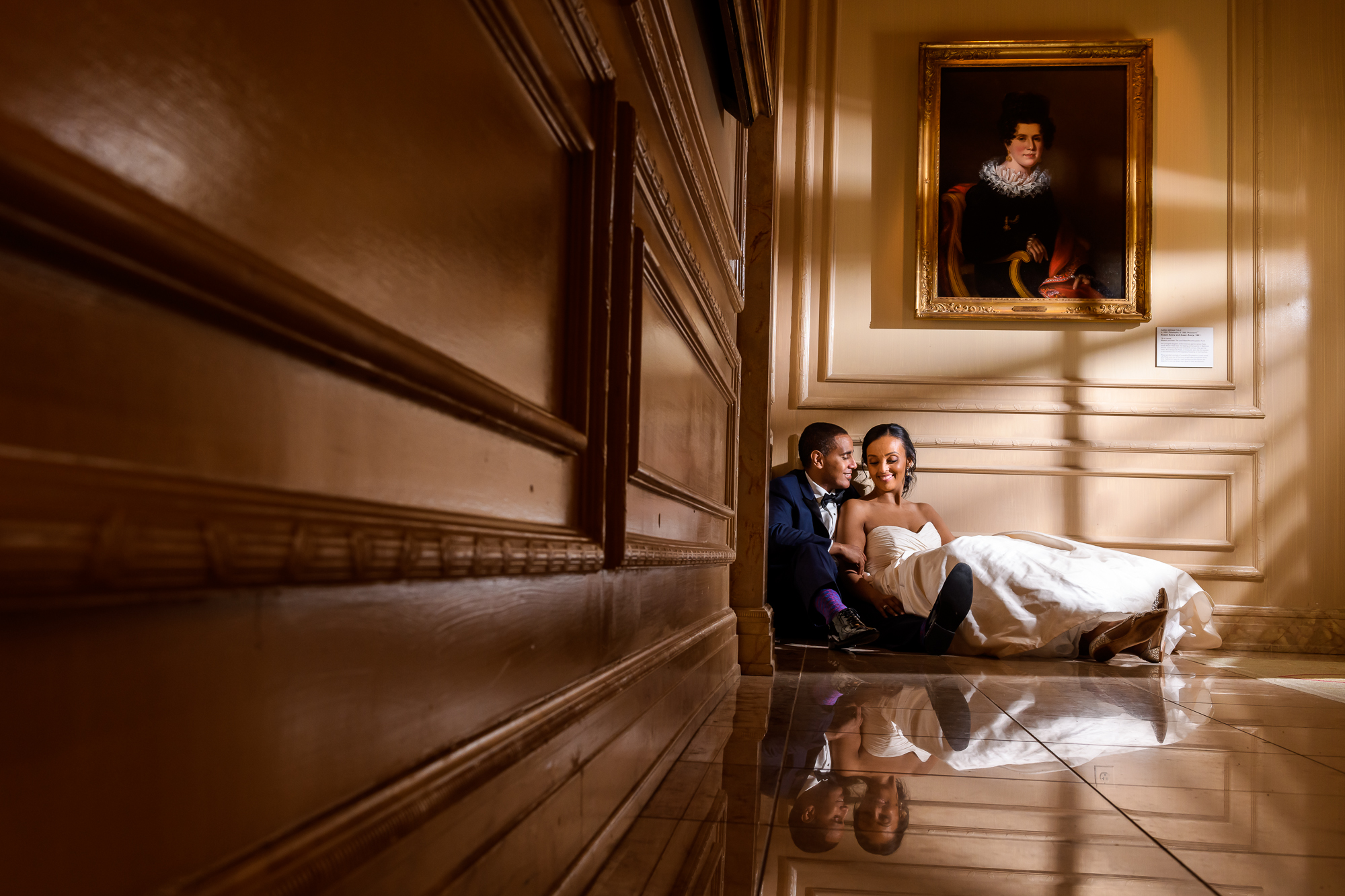 Bride and groom snuggling on marble floor - photo by Christopher Jason Studios