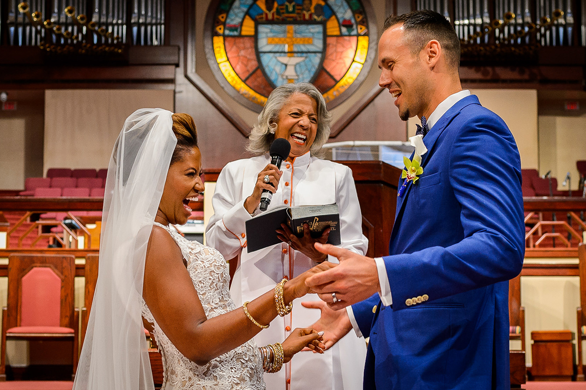 Bride and officiant laughing with groom during ceremony - photo by Christopher Jason Studios