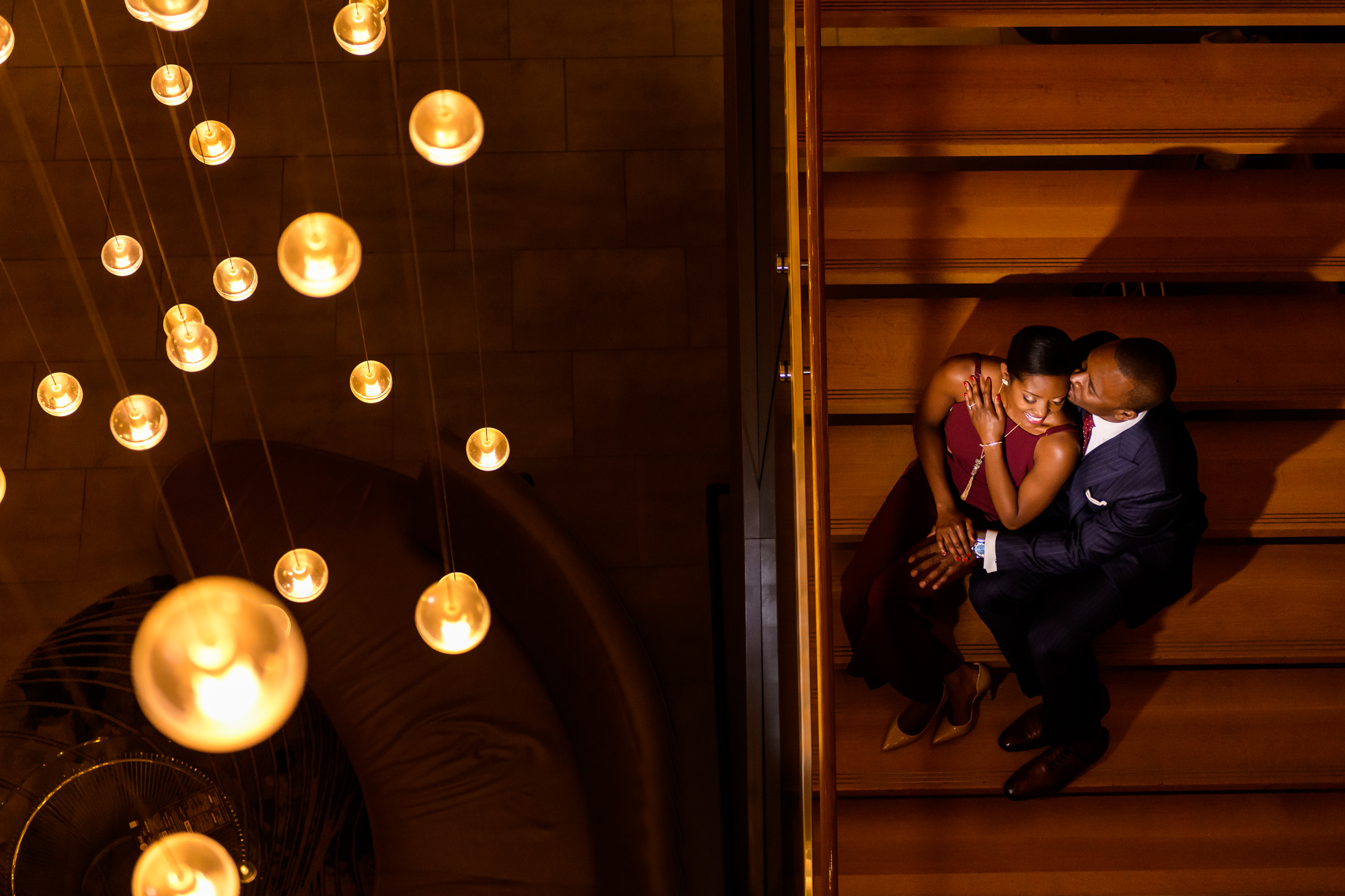 Creative composition of couple seated on stairway against hanging globe lights - photo by Christopher Jason Studios
