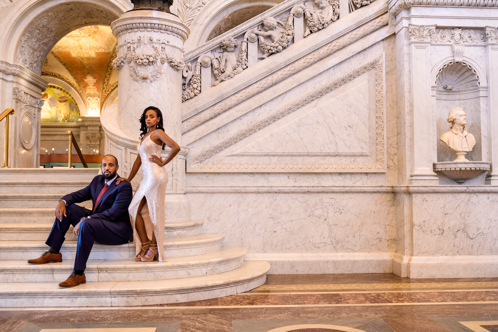 Elegant portrait of bride with slit silk dress on marble stairway with groom - photo by Christopher Jason Studios