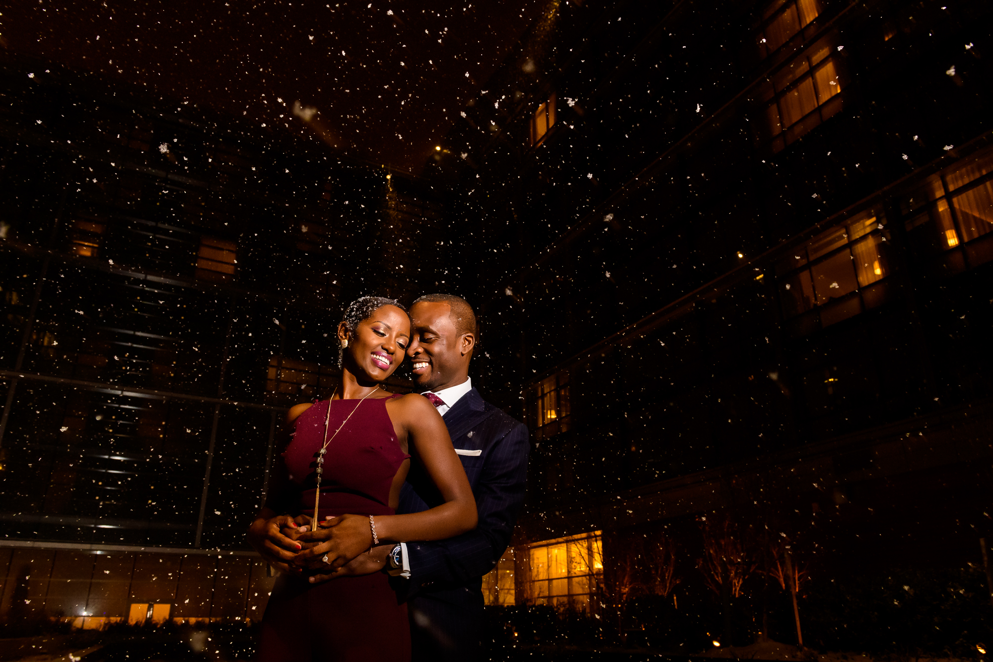 Engagement couple embrace in falling snow - photo by Christopher Jason Studios