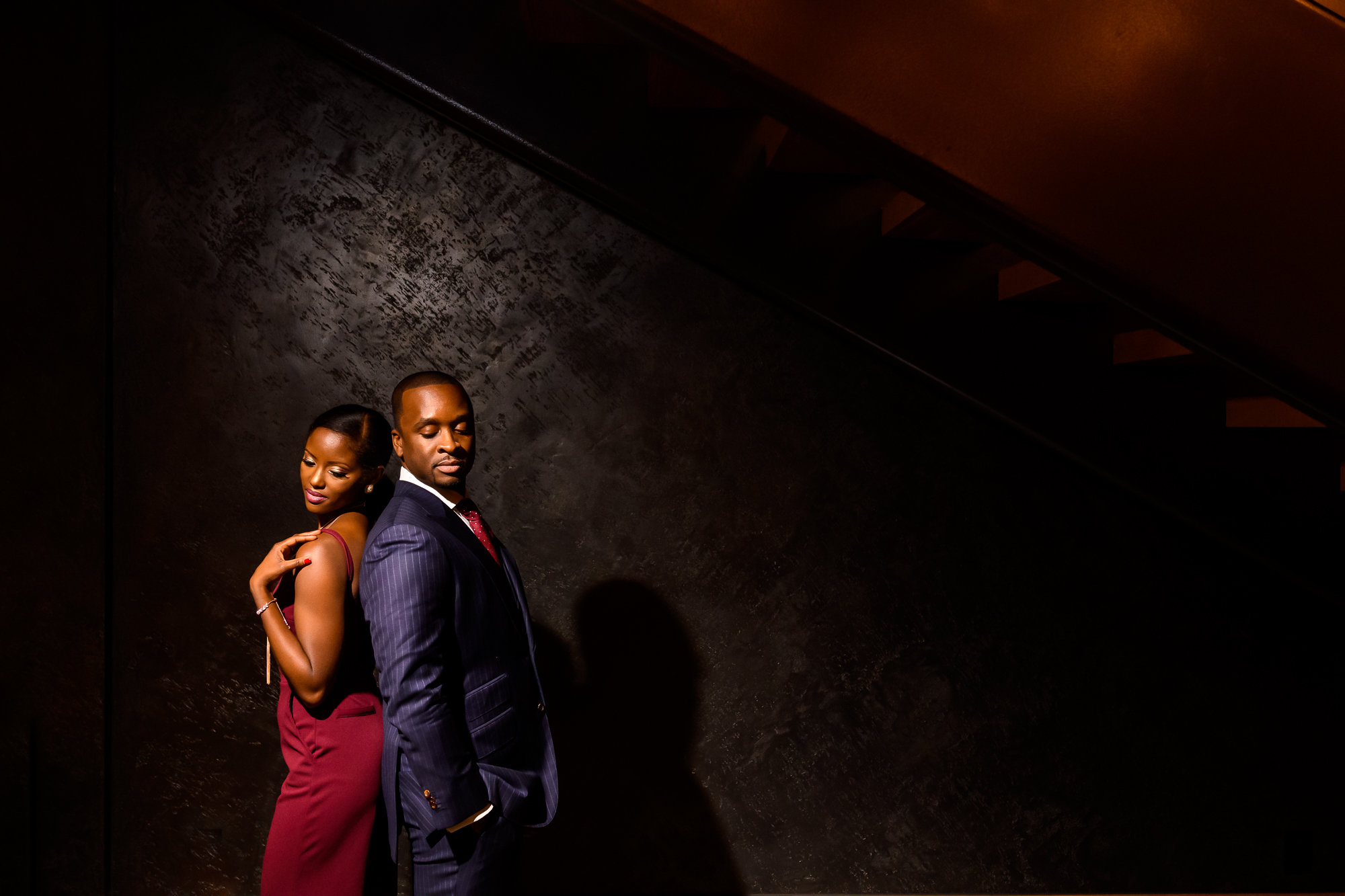 Engagement photo of couple back to back in spotlight - photo by Christopher Jason Studios