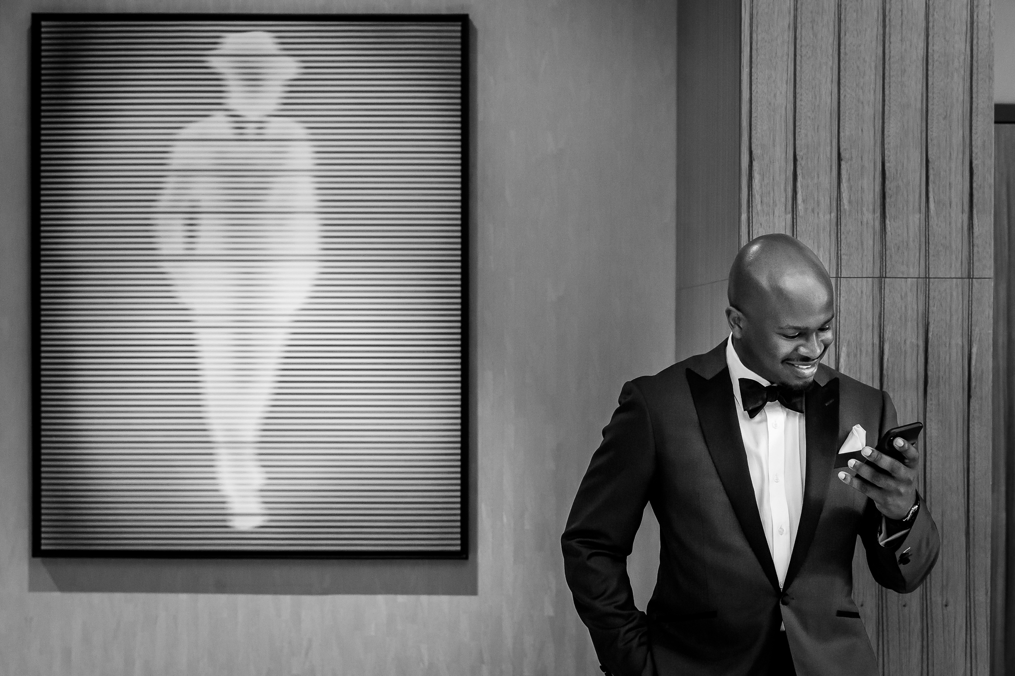 Groom checks his phone in front of fashion silhouette - photo by Christopher Jason Studios