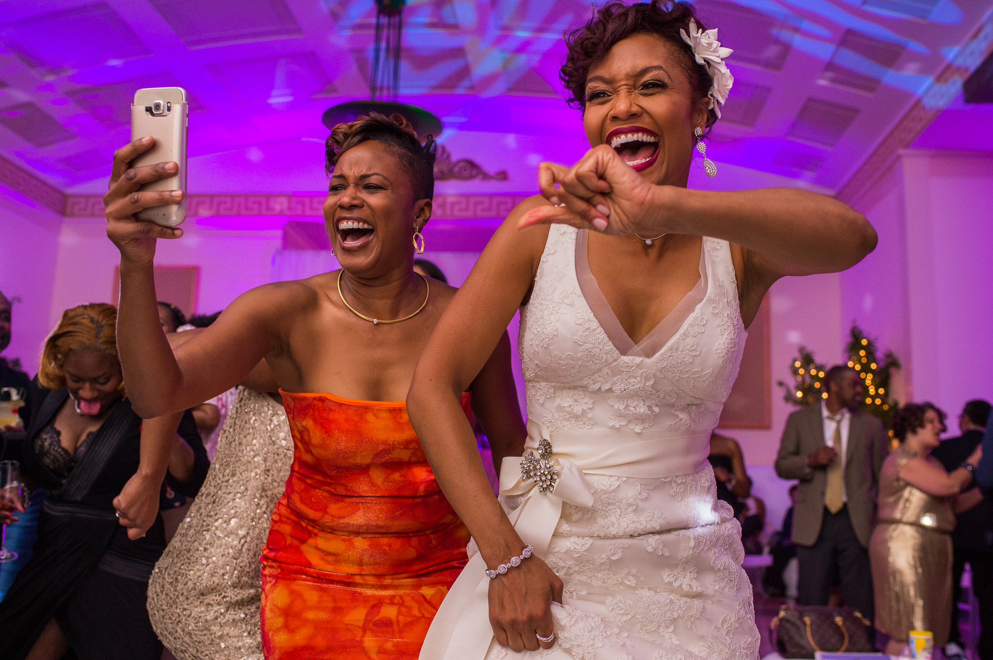 Happy bride dancing with bridesmaid taking a selfie - photo by Christopher Jason Studios
