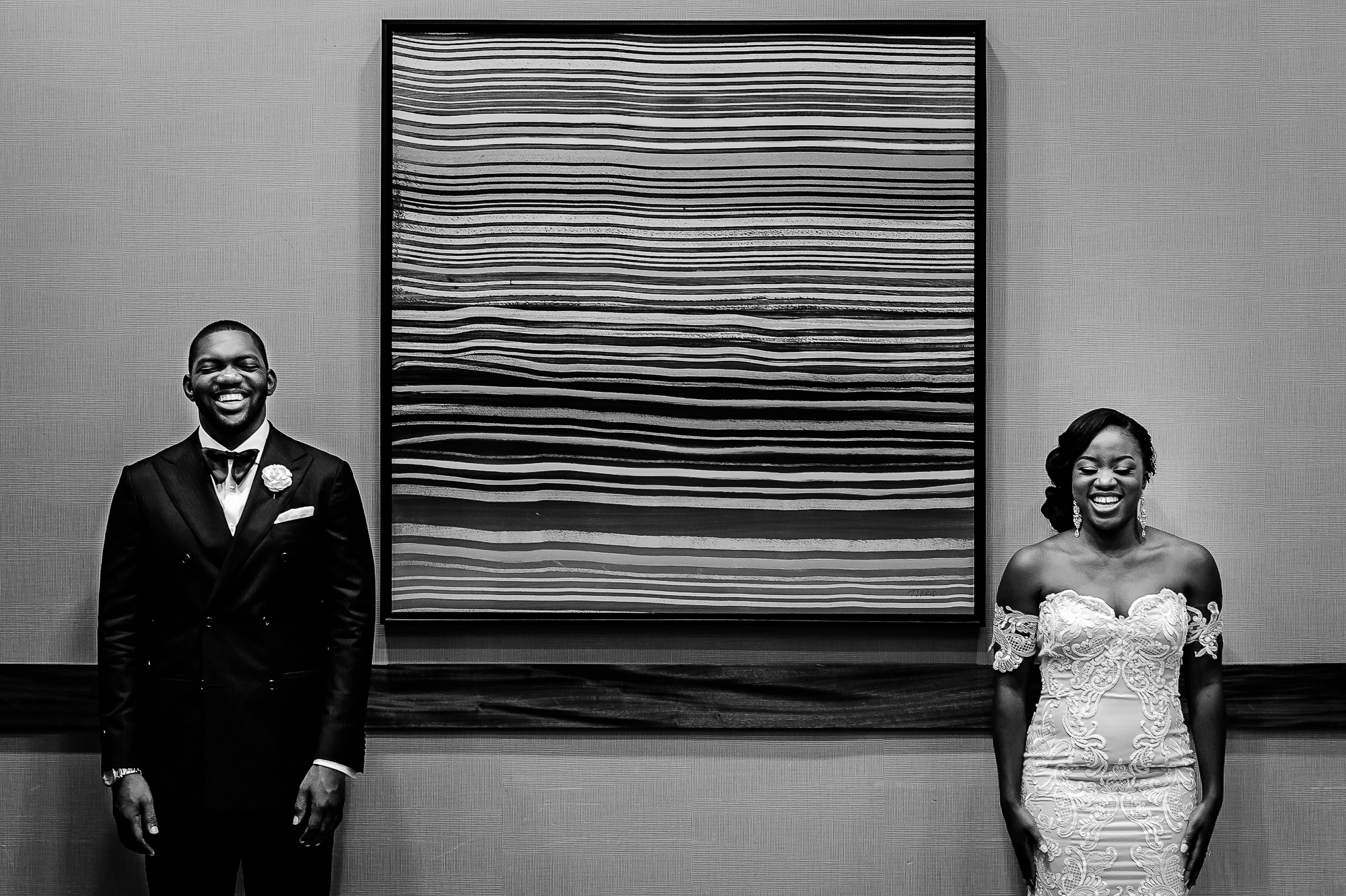 Smiling couple separated by abstract wall art - photo by Christopher Jason Studios