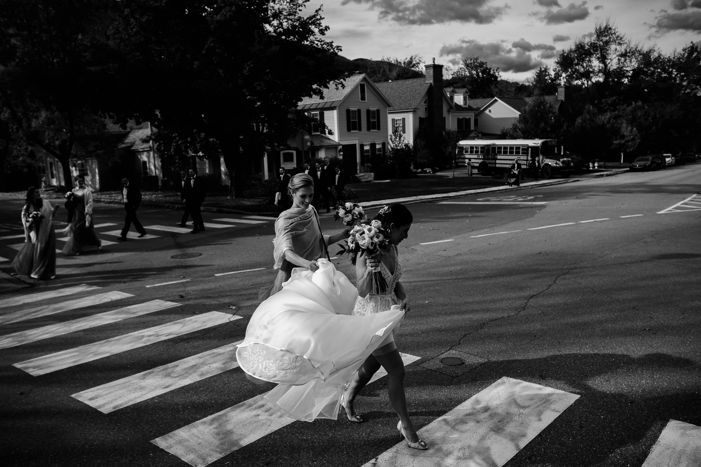 bride and bridesmaid walking to ceremony across crosswalk- photo by Hannah Photography