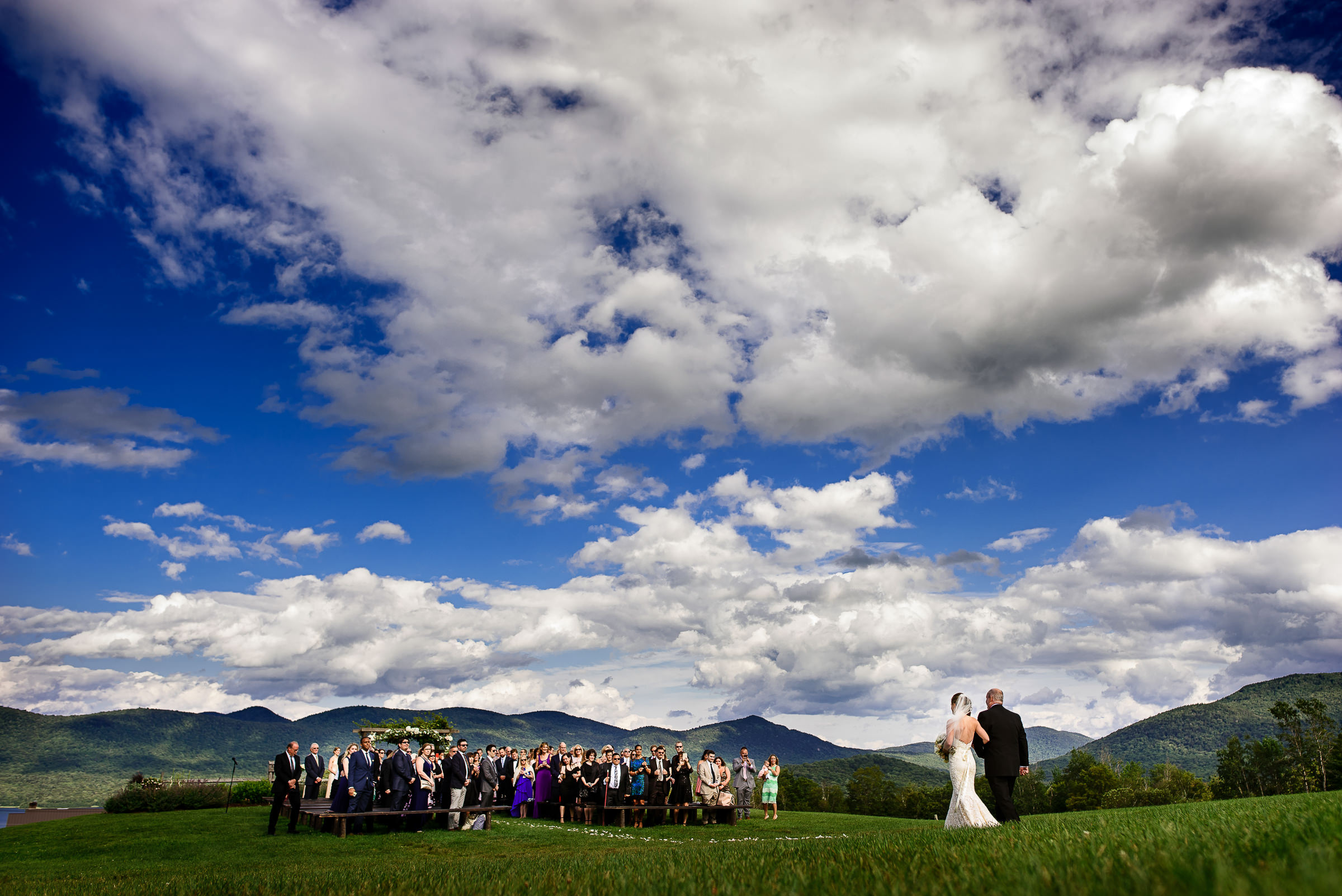 Bride and dad walking towards ceremony with gorgeous landscape - photo by Hannah Photography