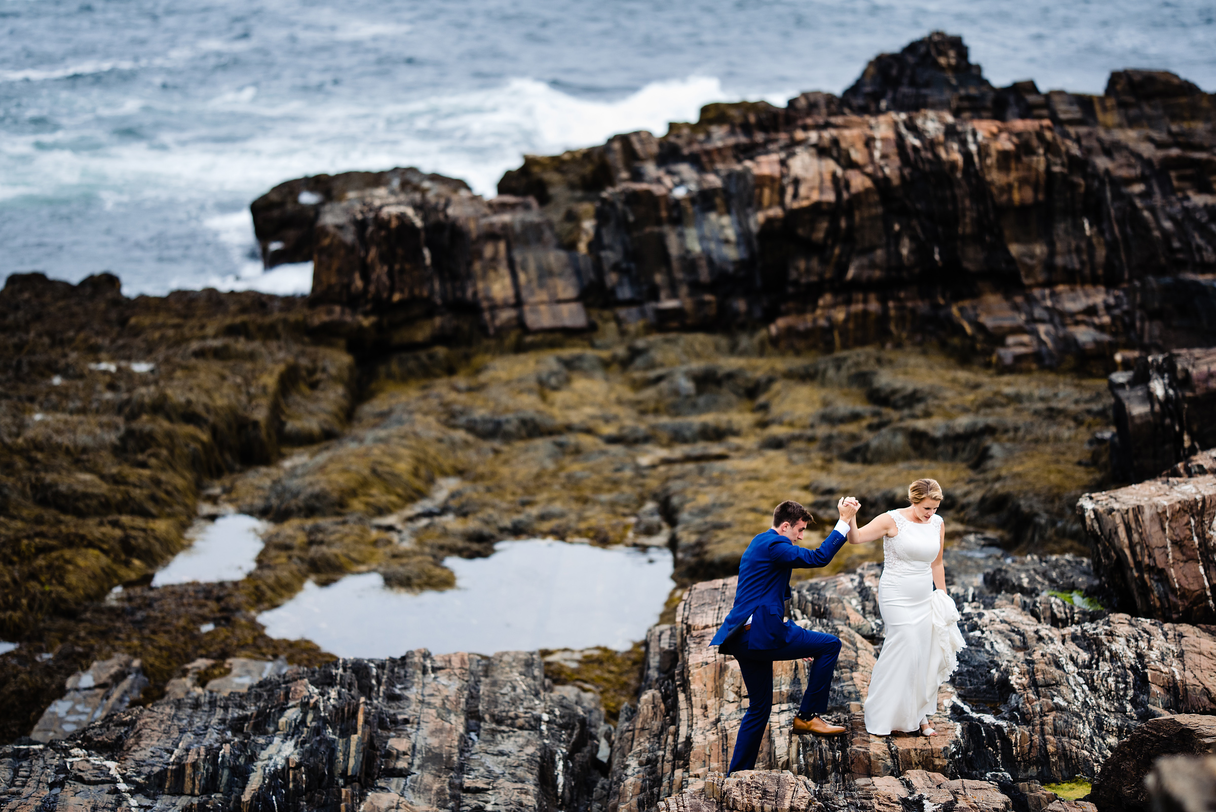 bride and groom climbing rocks on a snowy winter day- photo by Hannah Photography
