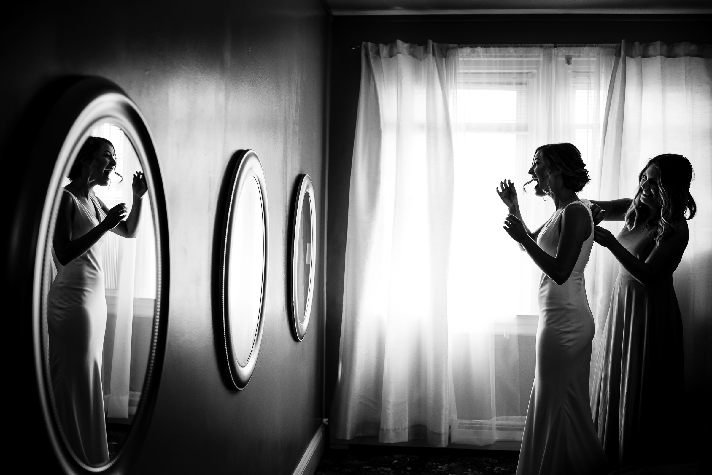 bride excited to get her dress on with help from her maid of honor- photo by Hannah Photography