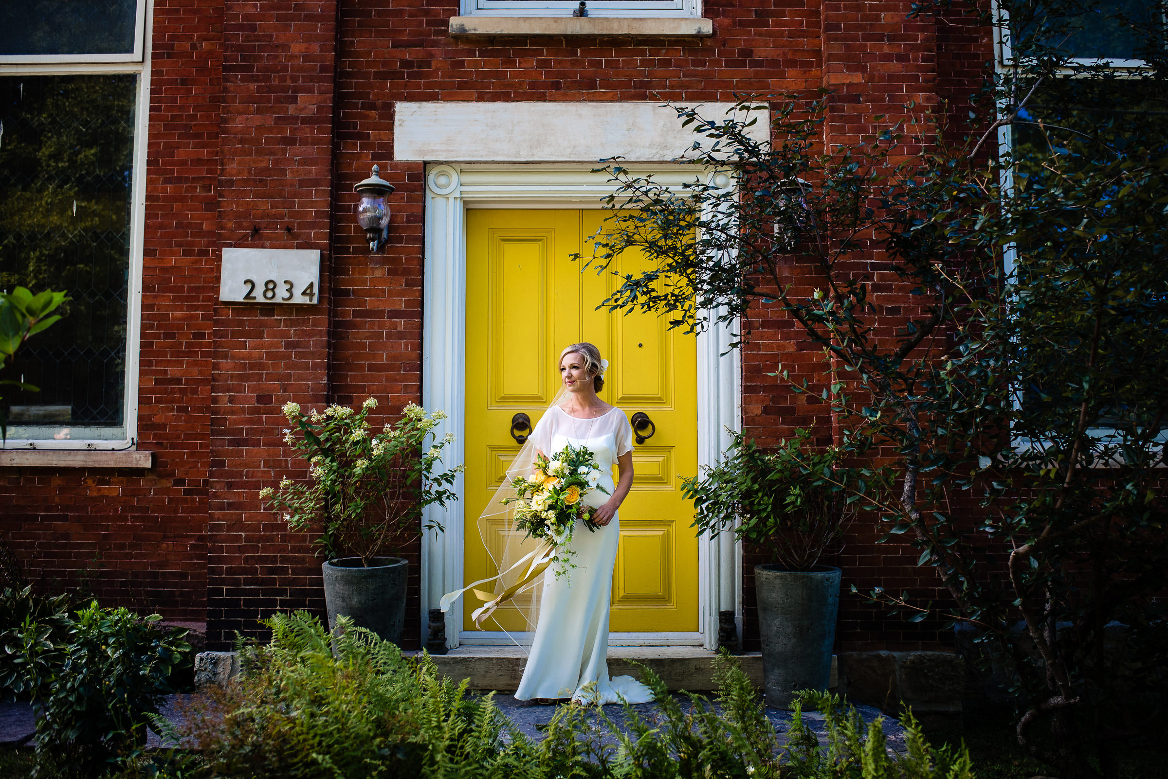 bride portrait in front of yellow front door- photo by Hannah Photography