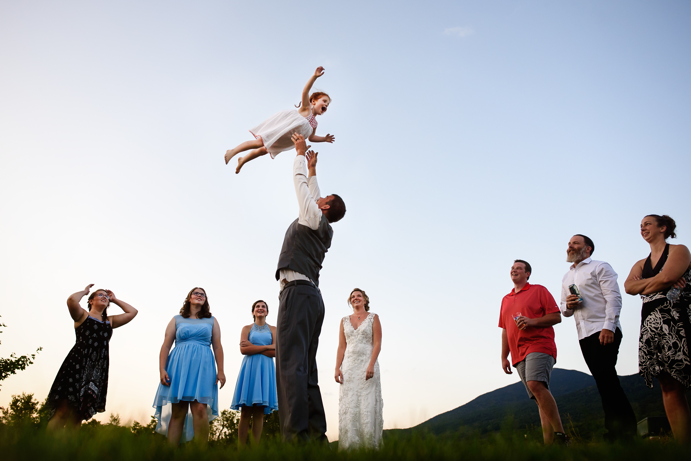 groom throwing the flower girl in the sky for fun- photo by Hannah Photography