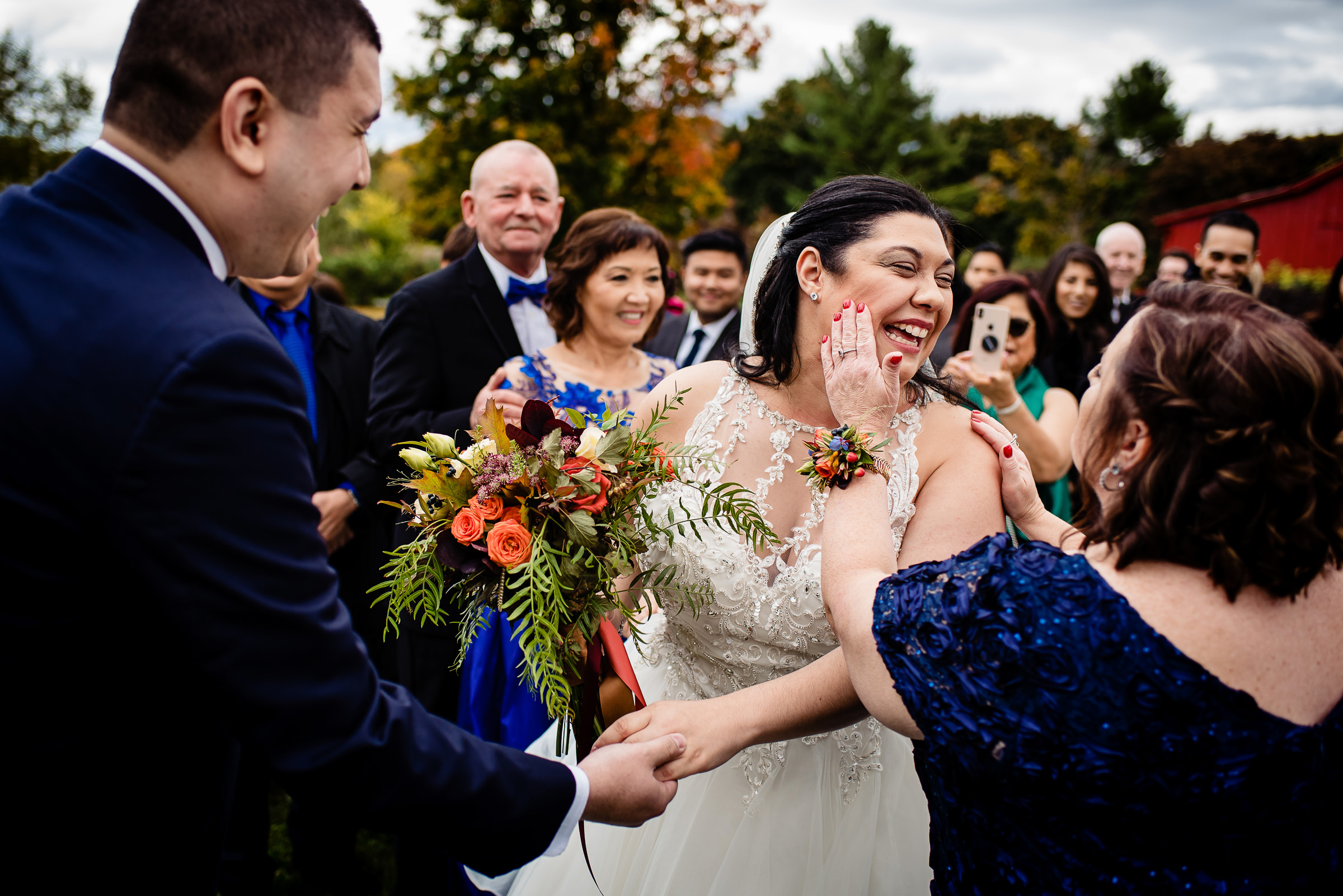 Mother touches happy bride's cheeks during ceremony - photo by Hannah Photography