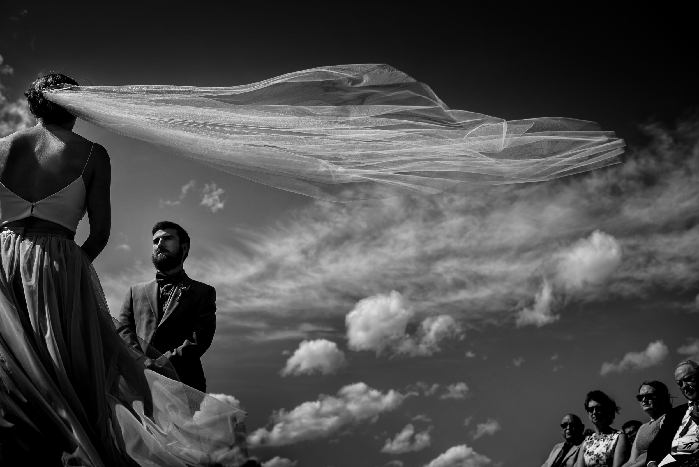 Veil flying in the wind during ceremony - photo by Hannah Photography