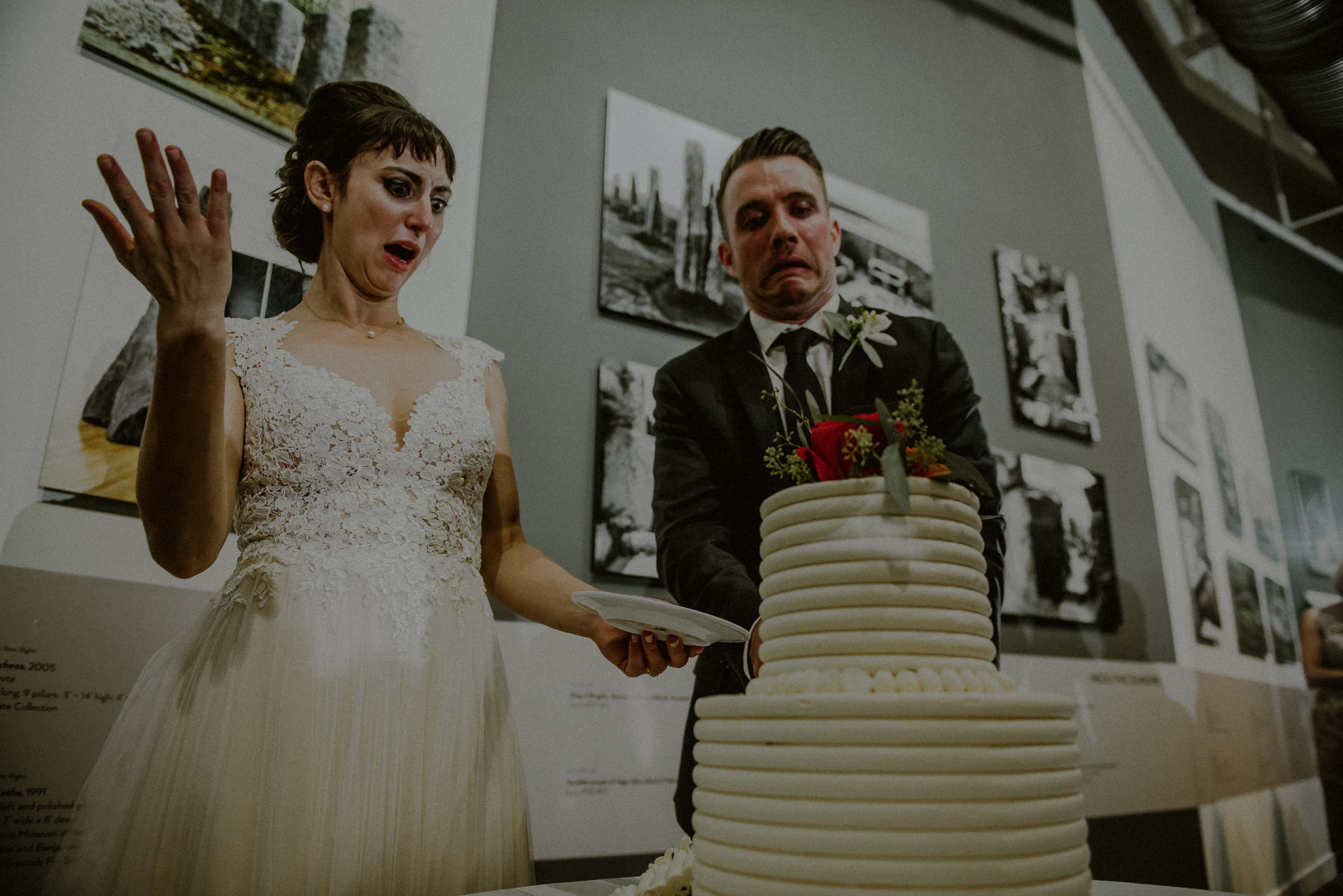 Comical portrait of couple cutting tiered cake - photo by Carolina Rivera Photography