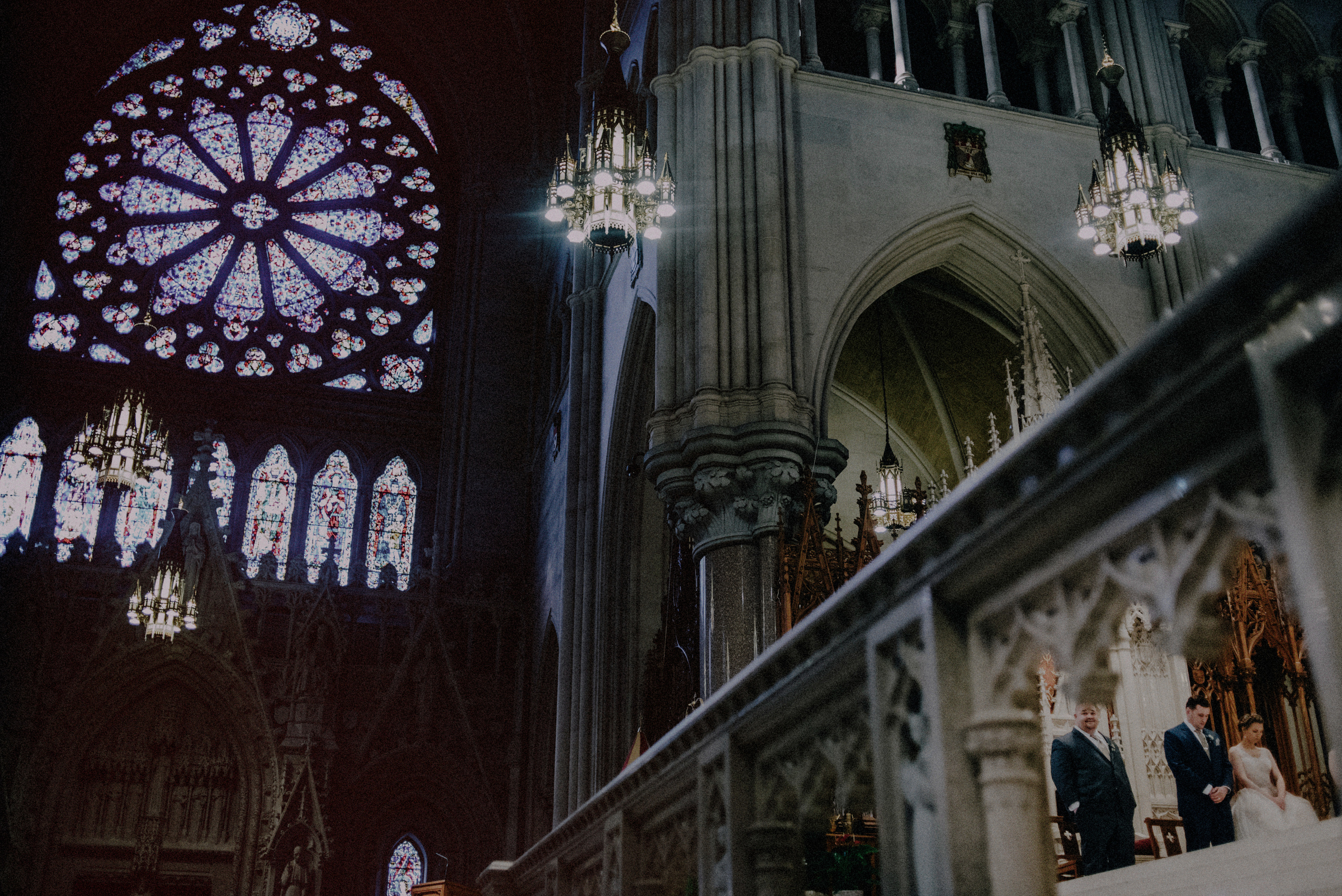 Couple in cathedral against rose window - photo by Carolina Rivera Photography
