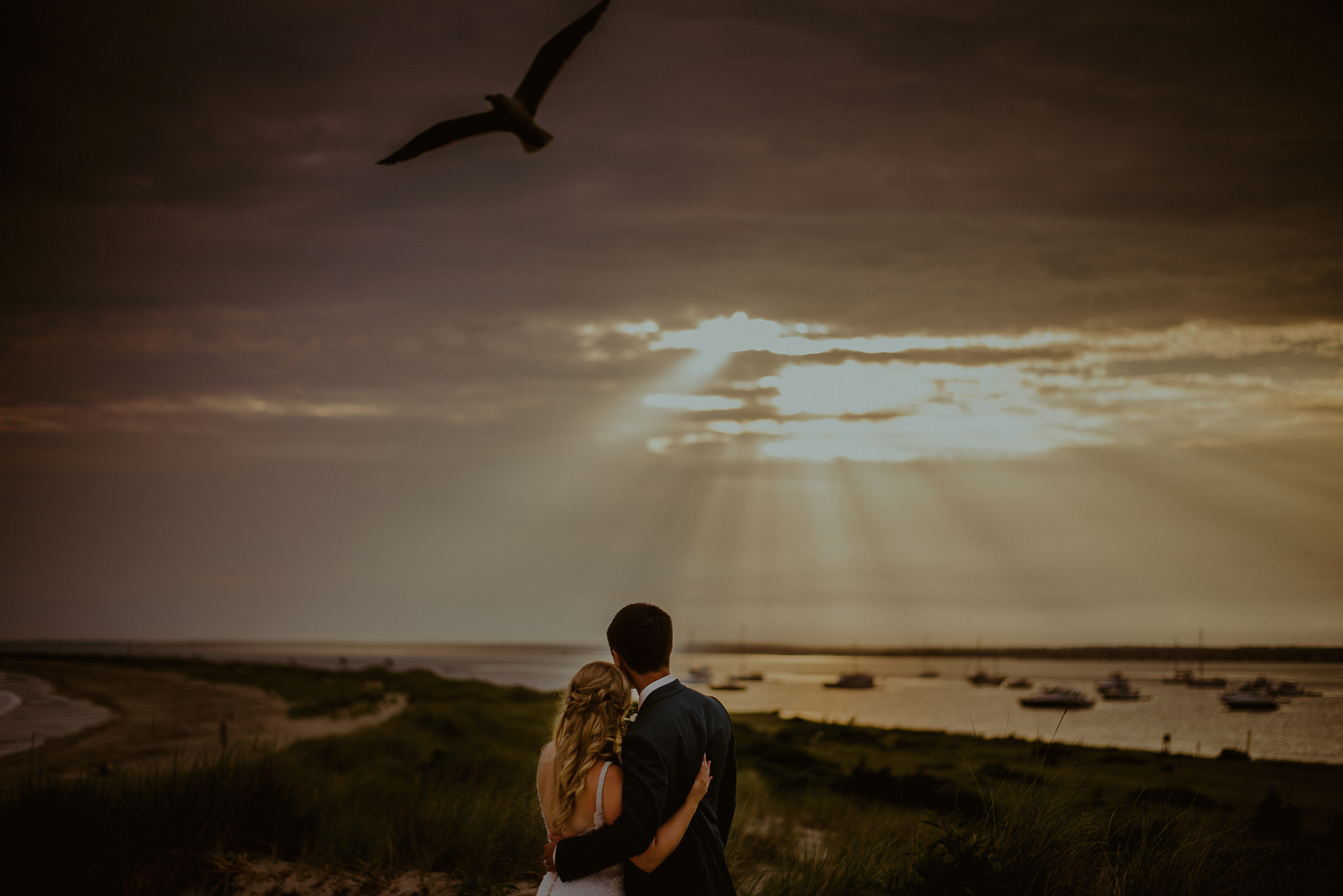 Couple looking out at sun rays on the water - photo by Carolina Rivera Photography