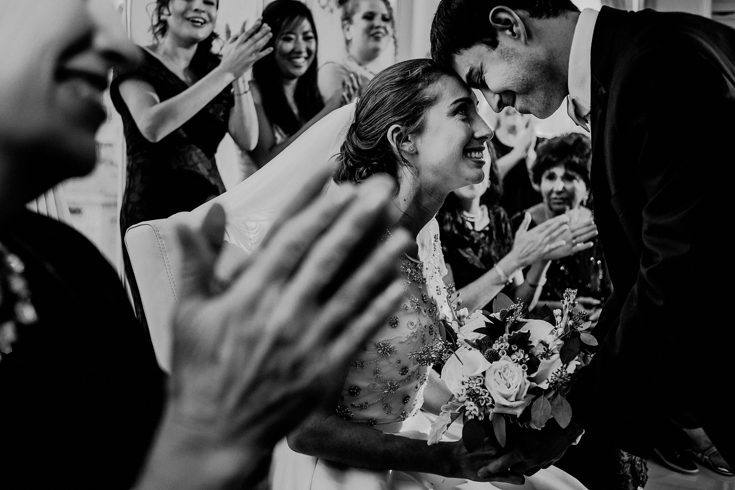 Groom bends to seated bride - photo by Carolina Rivera Photography