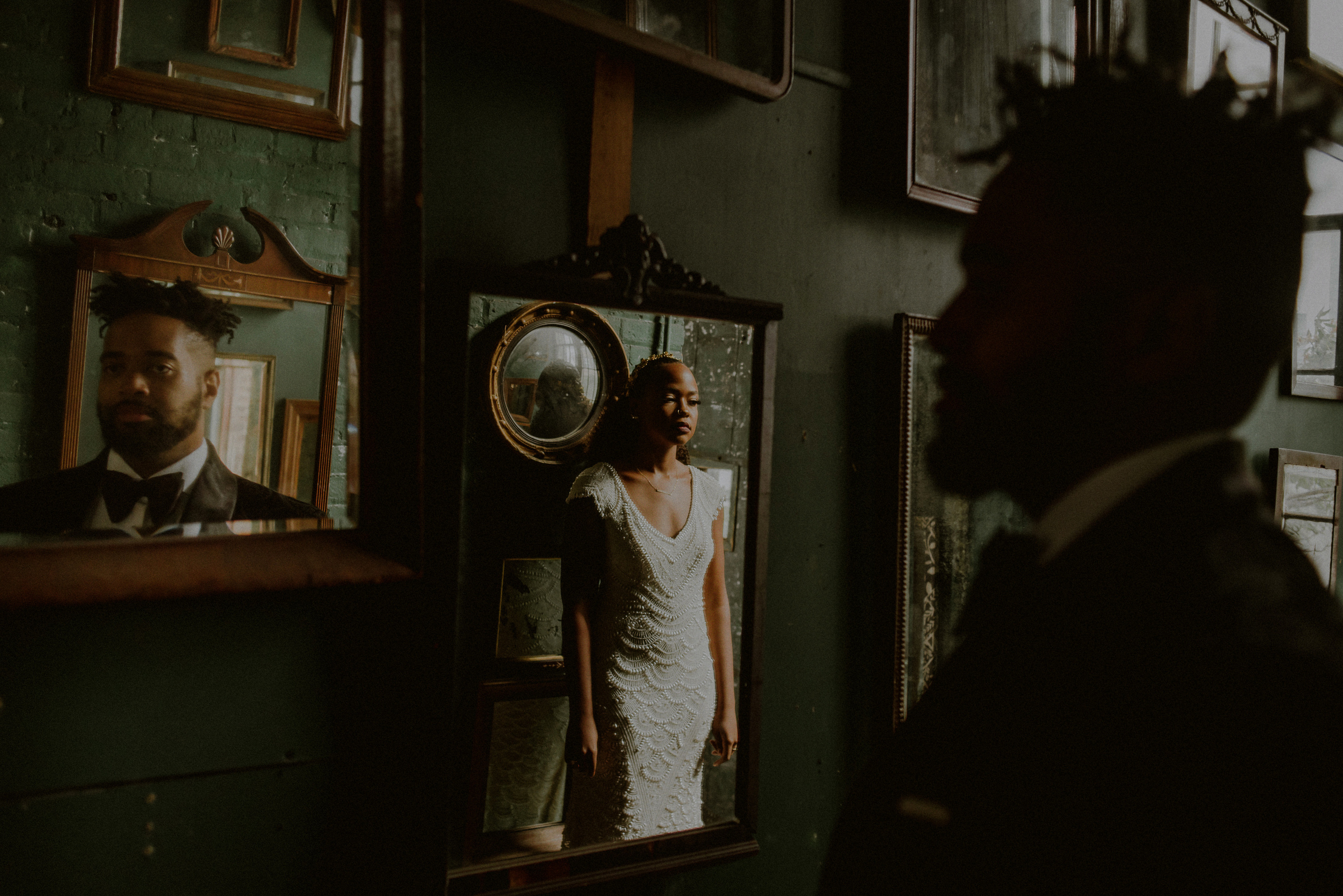 Solemn bride with groom reflected in gallery - photo by Carolina Rivera Photography