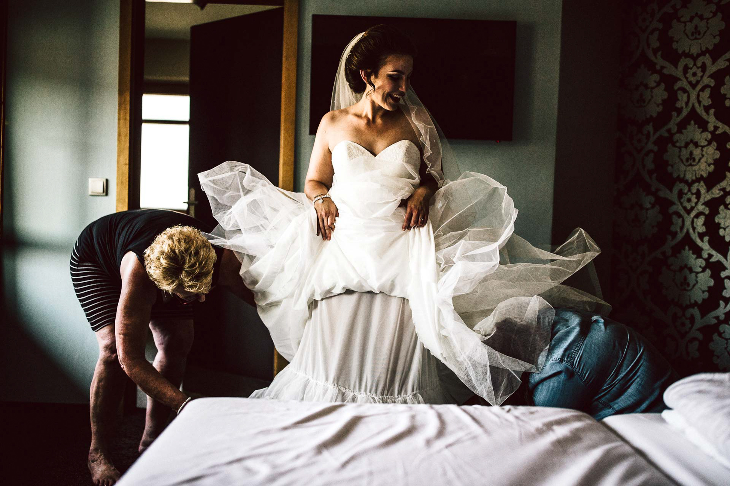 bride happily getting her dress on with help by mom - photo by FineArt Weddings | Photography