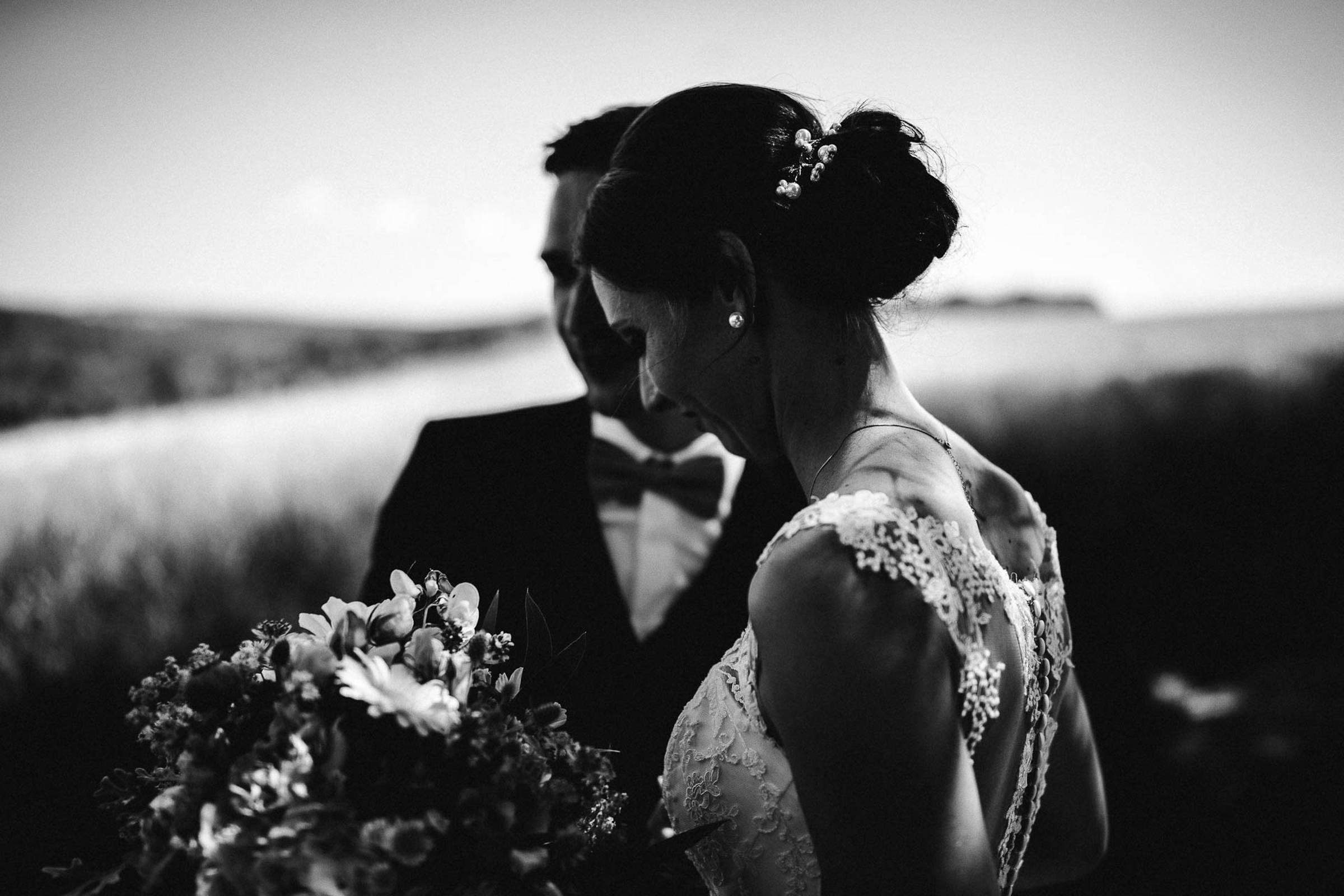 black and white image of bride and groom in field- photo by FineArt Weddings   Photography