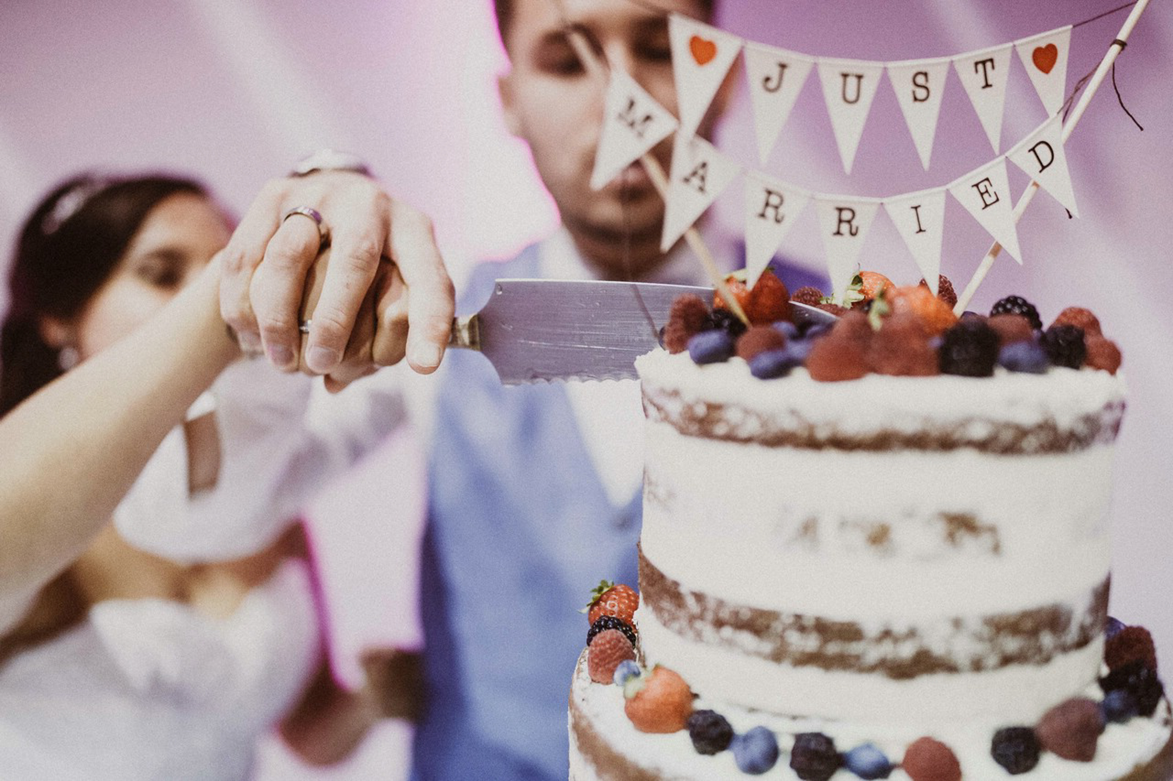 bride and groom cutting the cake full of berries- photo by FineArt Weddings | Photography