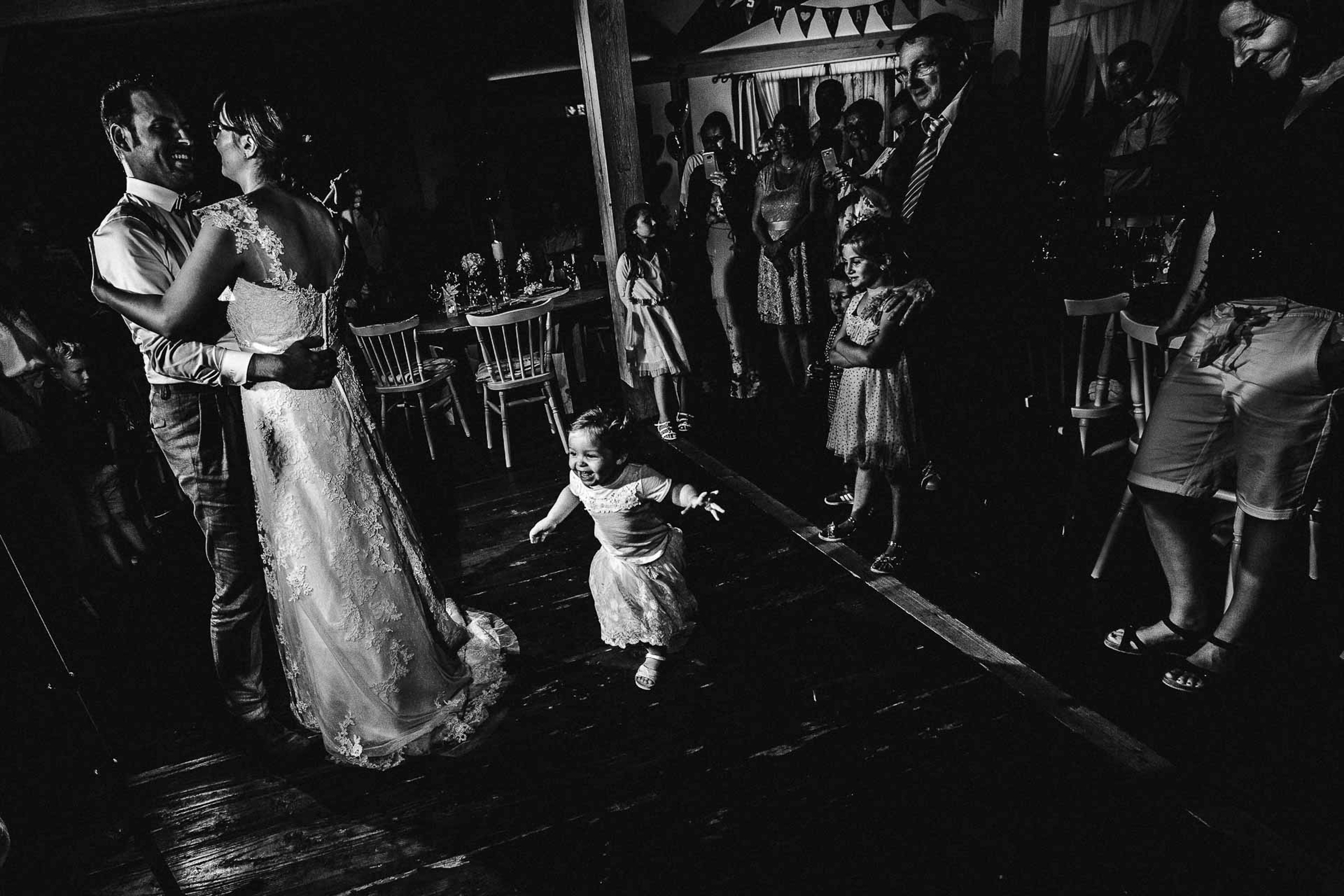 bride and groom first dance with cute little girl jumping in- photo by FineArt Weddings | Photography