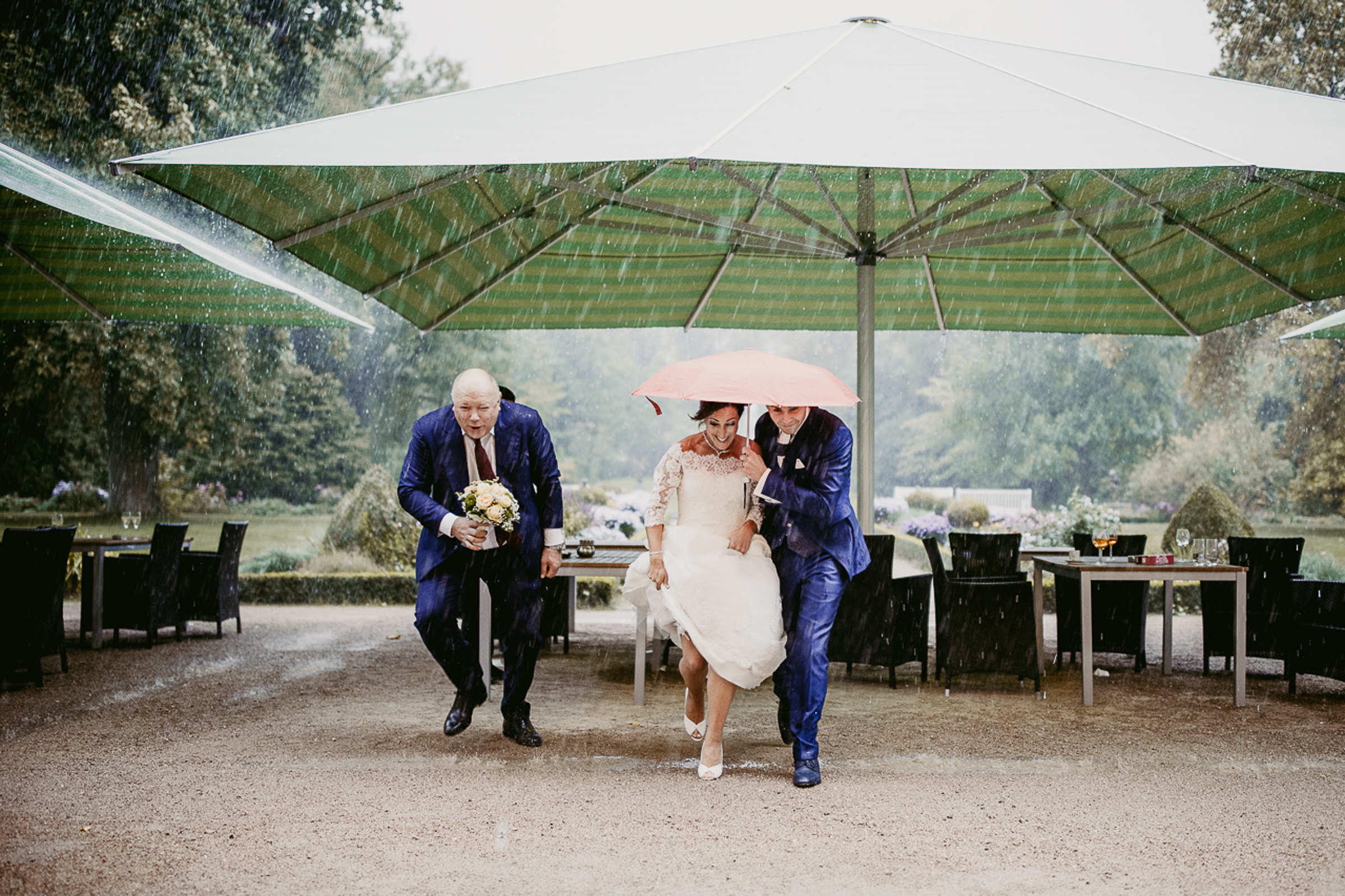 bride and groom running to avoid rain under umbrella- photo by FineArt Weddings | Photography