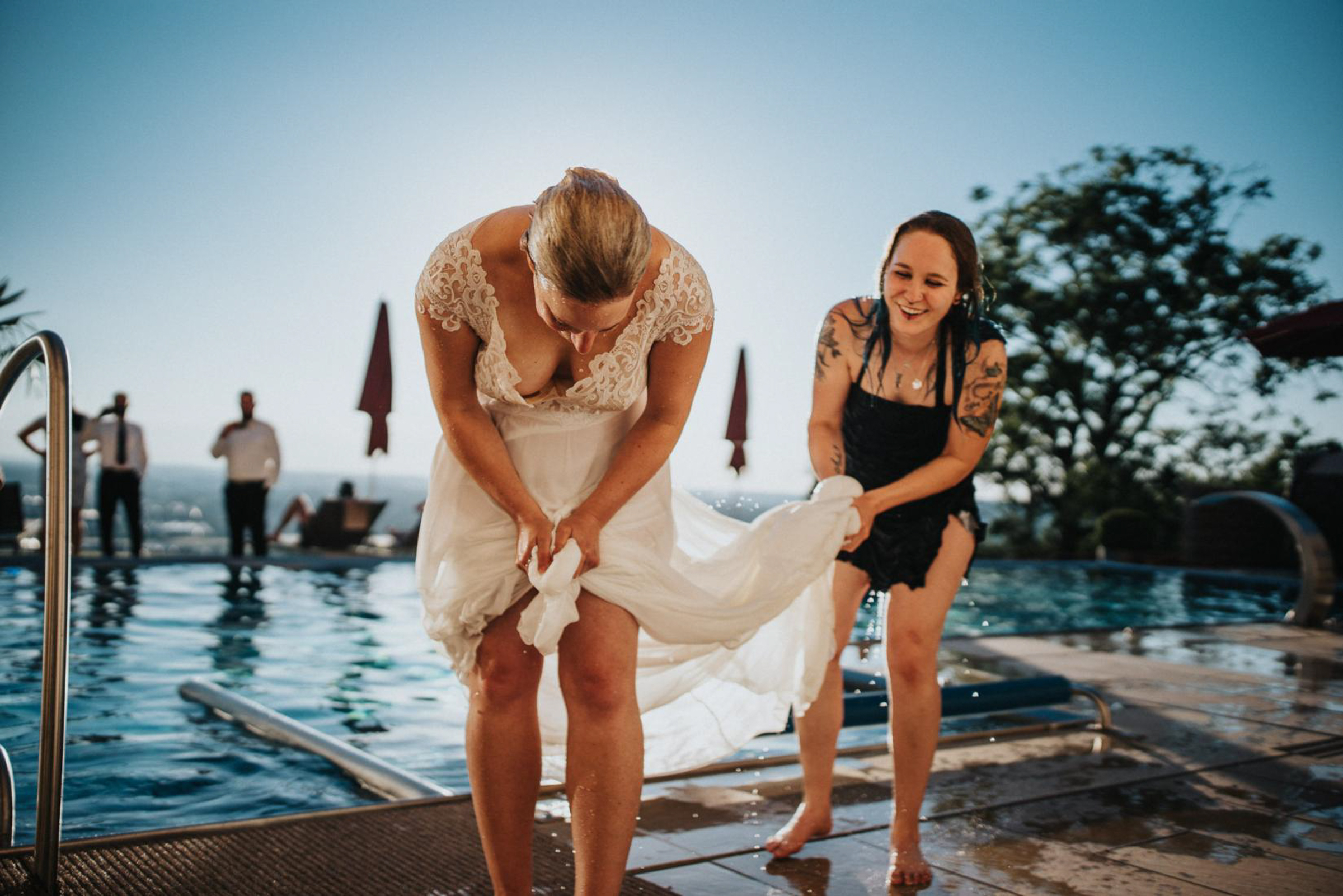 bride drying off after dip in pool with dress on- photo by FineArt Weddings | Photography