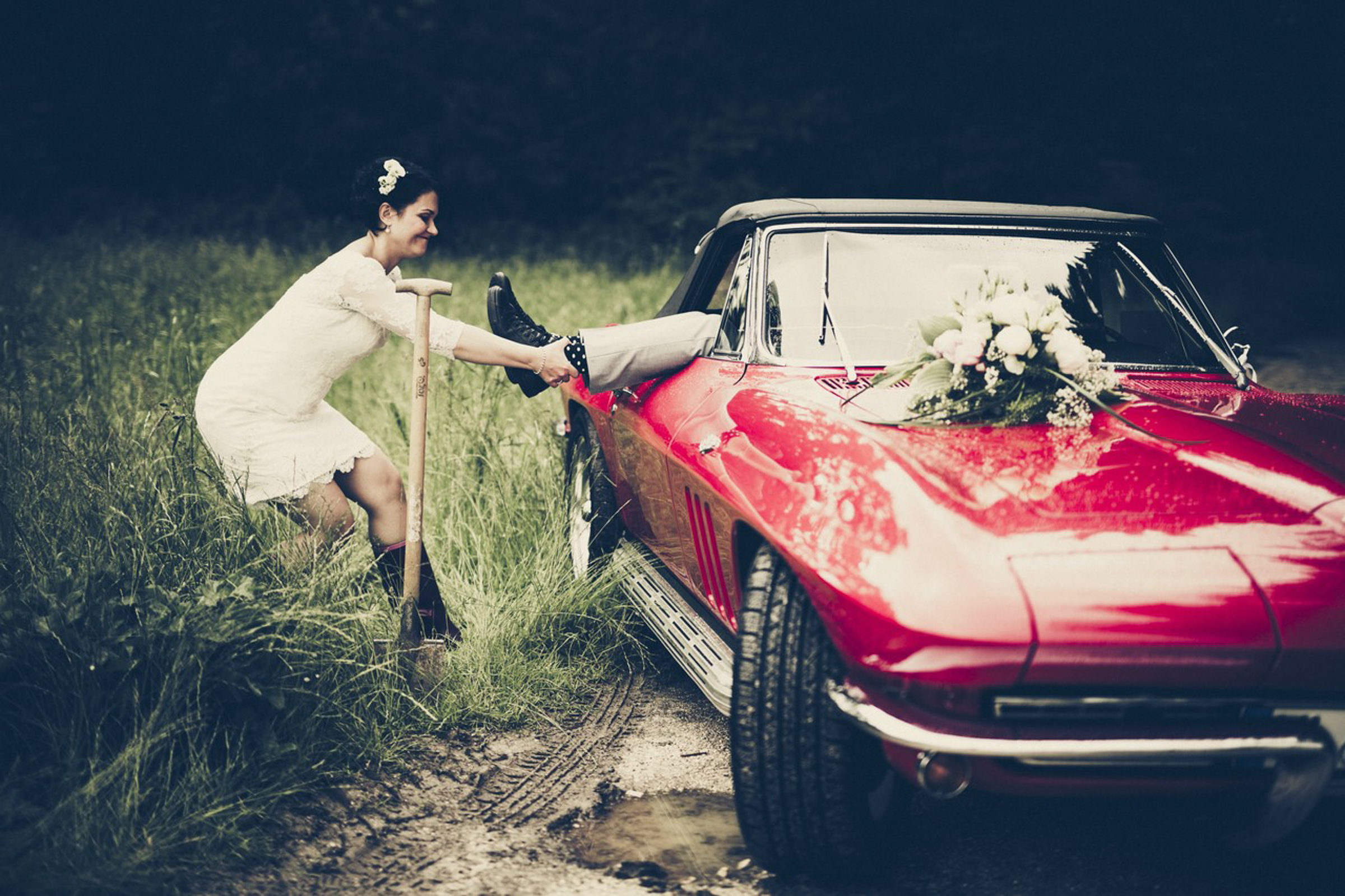 bride playing around pulling groom out of red corvette- photo by FineArt Weddings | Photography