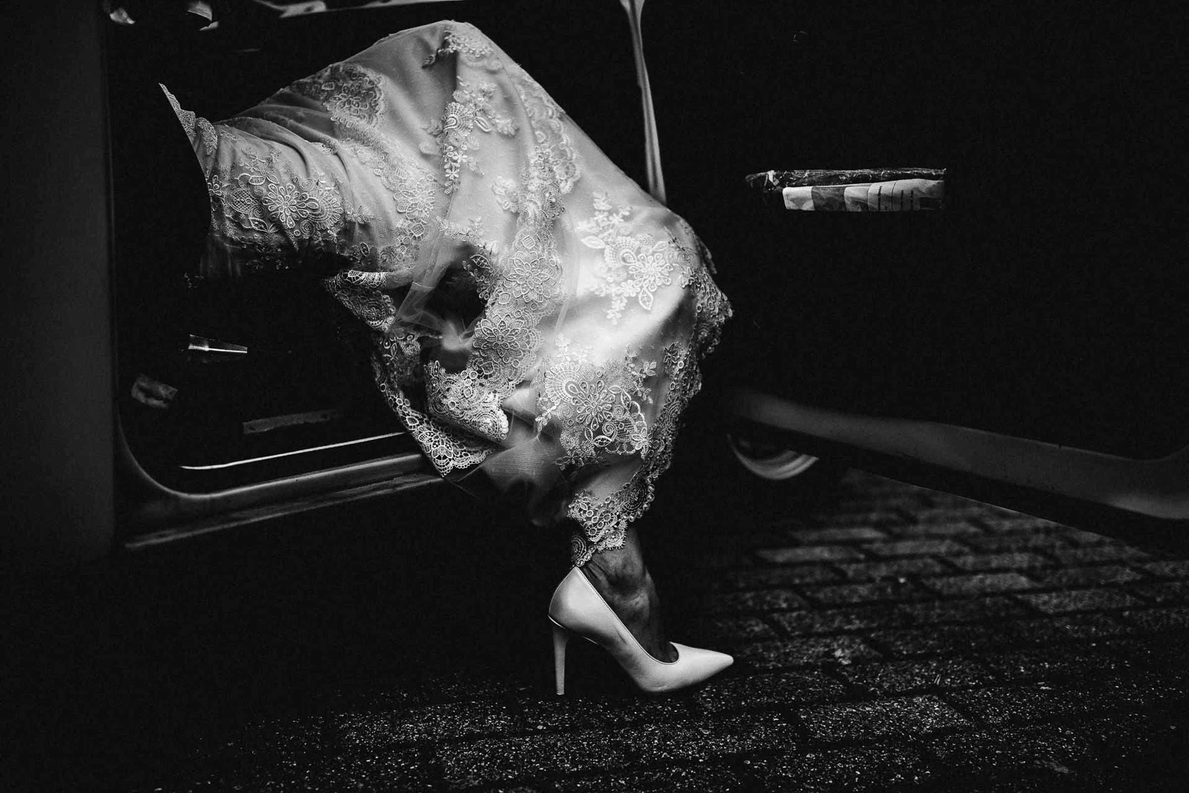 bride stepping out of car in white heels- photo by FineArt Weddings | Photography