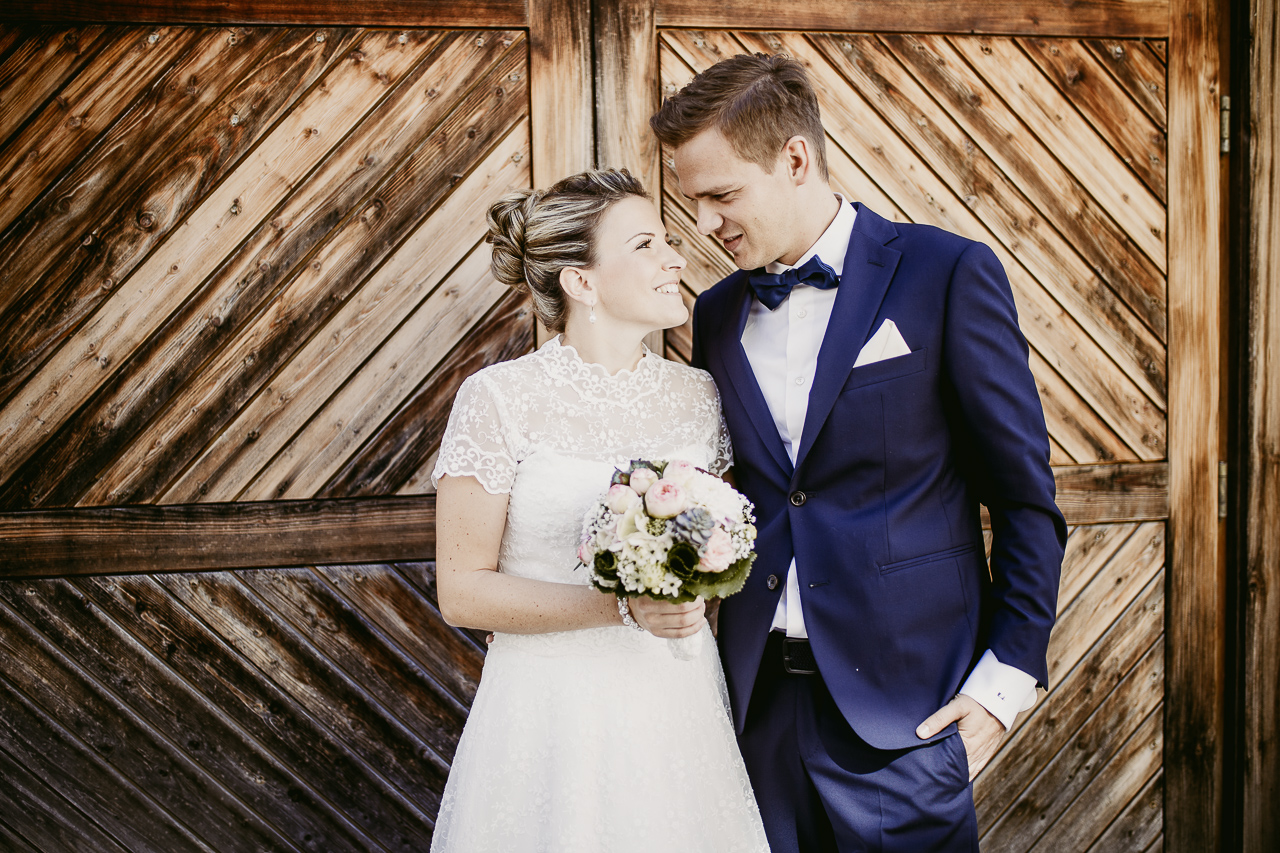 Couple against rustic wooden door - photo by FineArt Weddings | Photography