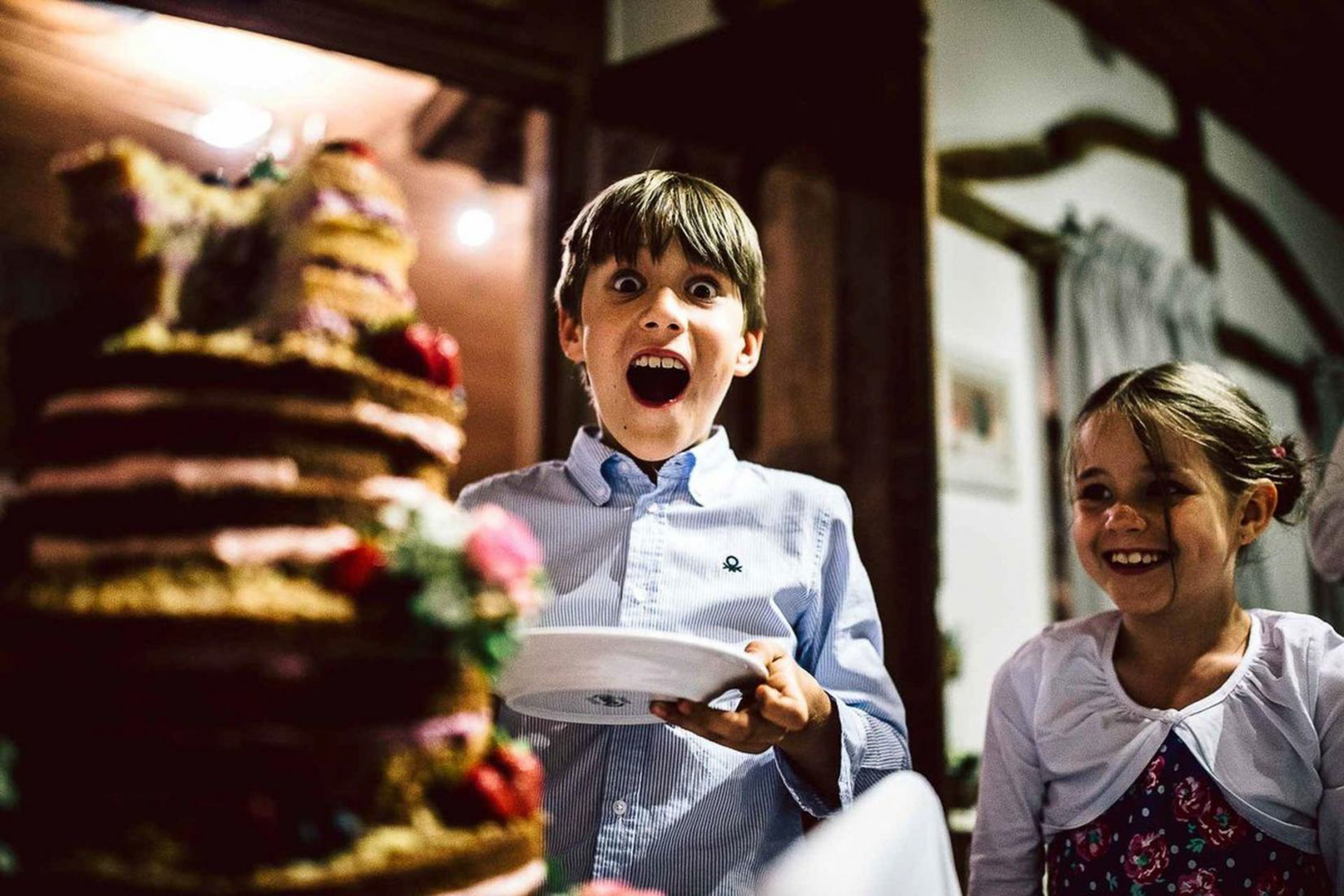 excited little boy waiting for bride and groom to cut the cake- photo by FineArt Weddings | Photography