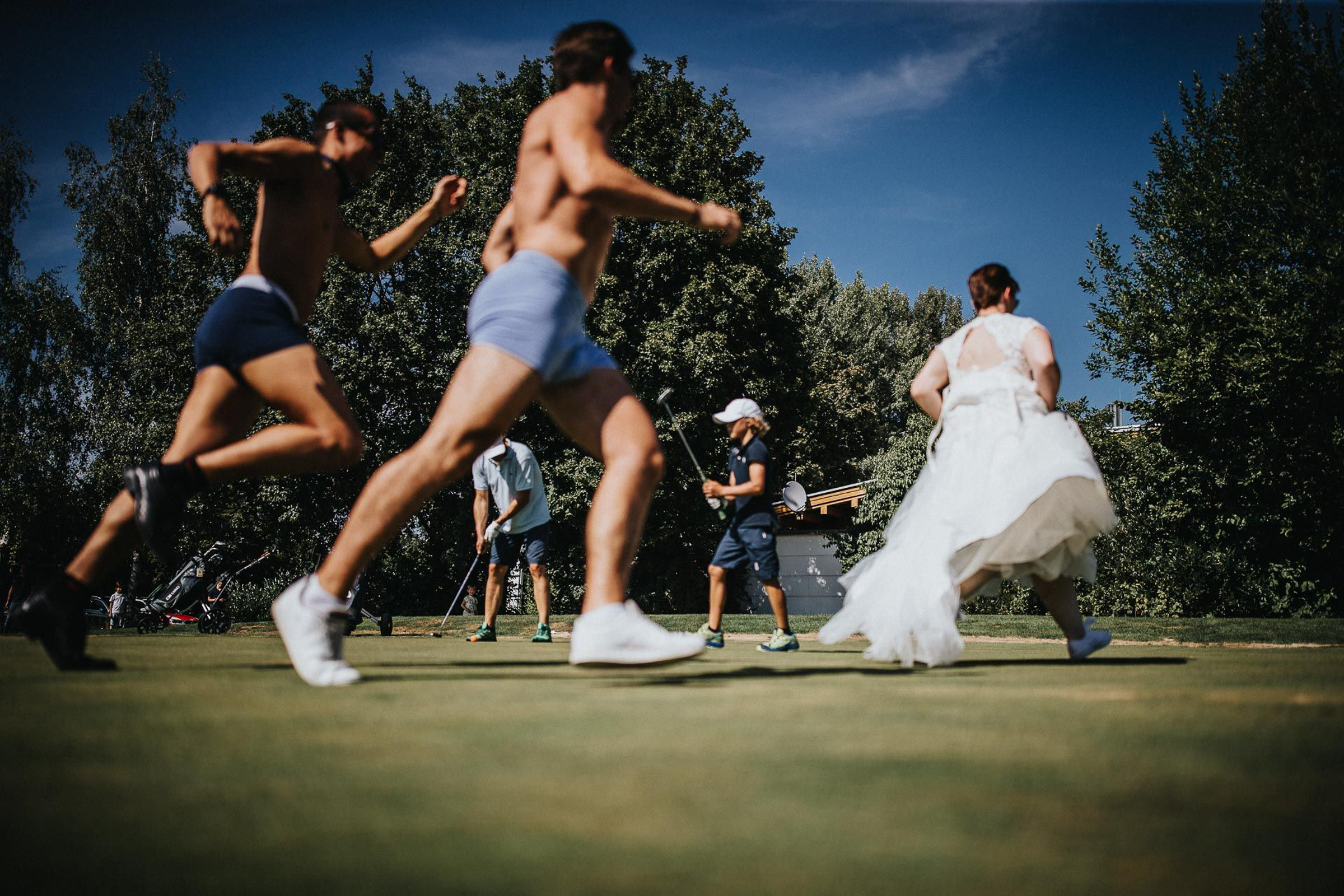 fun moment with bride running through golf course- photo by FineArt Weddings | Photography