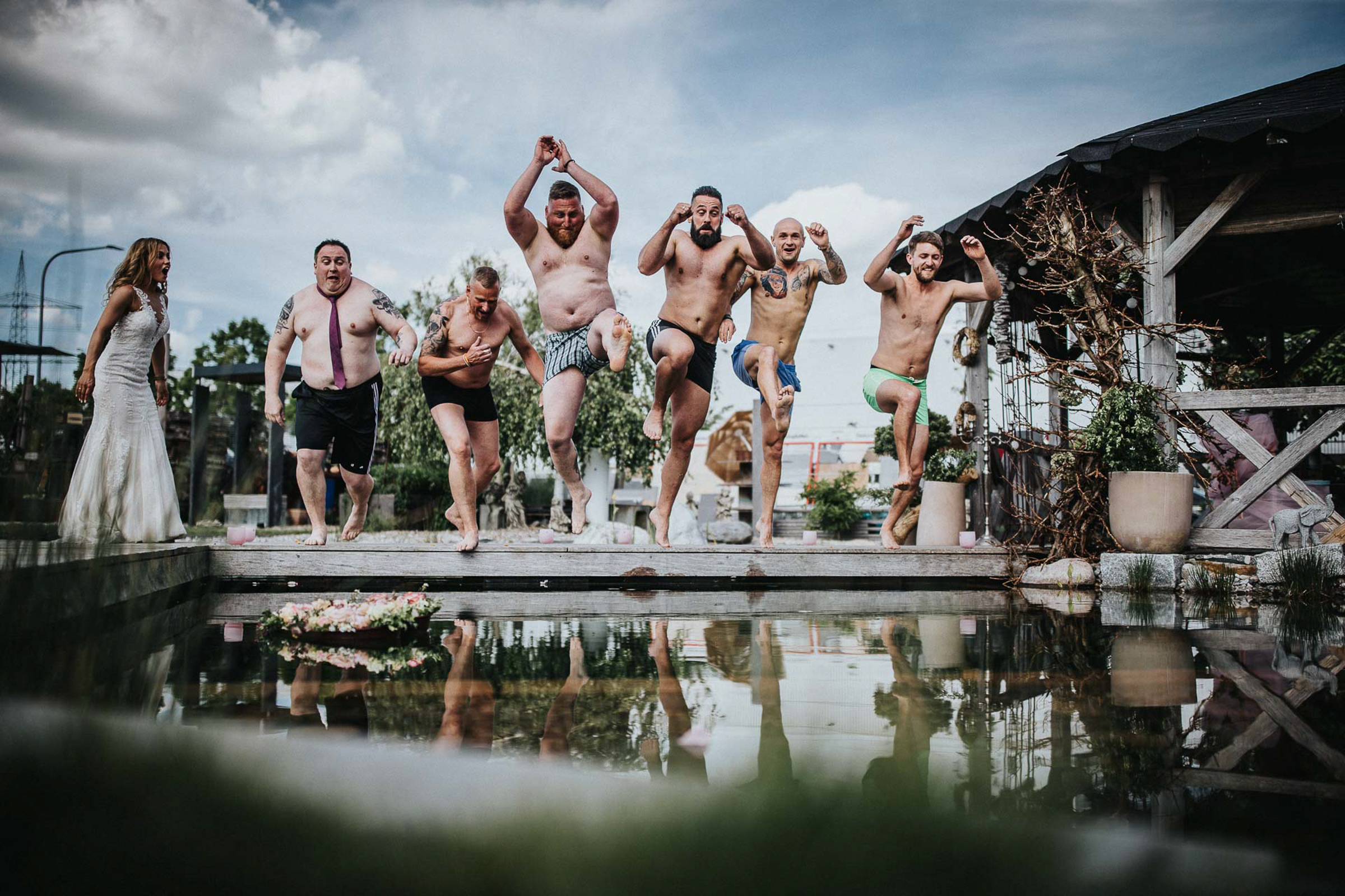 Groomsmen jump into pool next to bride - photo by FineArt Weddings - Germany